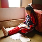 A girl sits on the floor of her living room reading a letter from her sponsor.