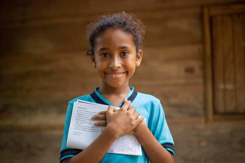 A girl clutches a letter to her chest.