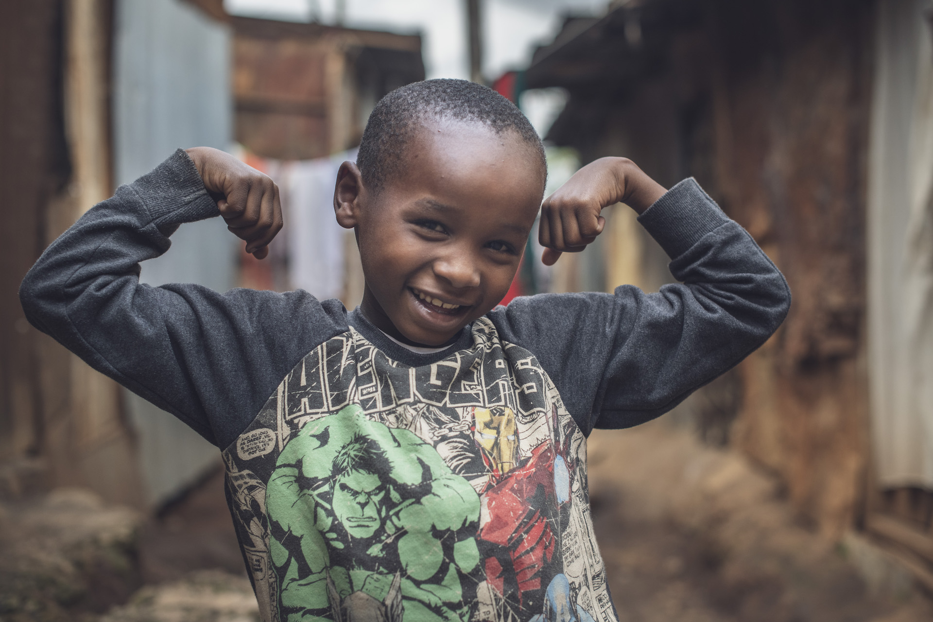 A boy stands flexing his arms.