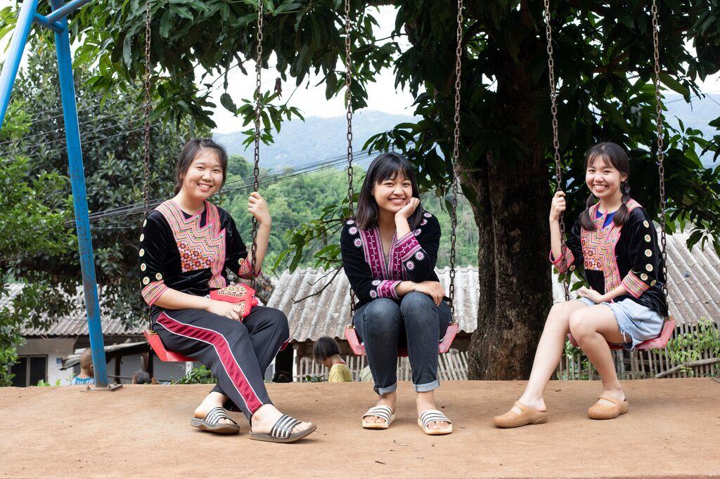 Three girls sit on a swing set.
