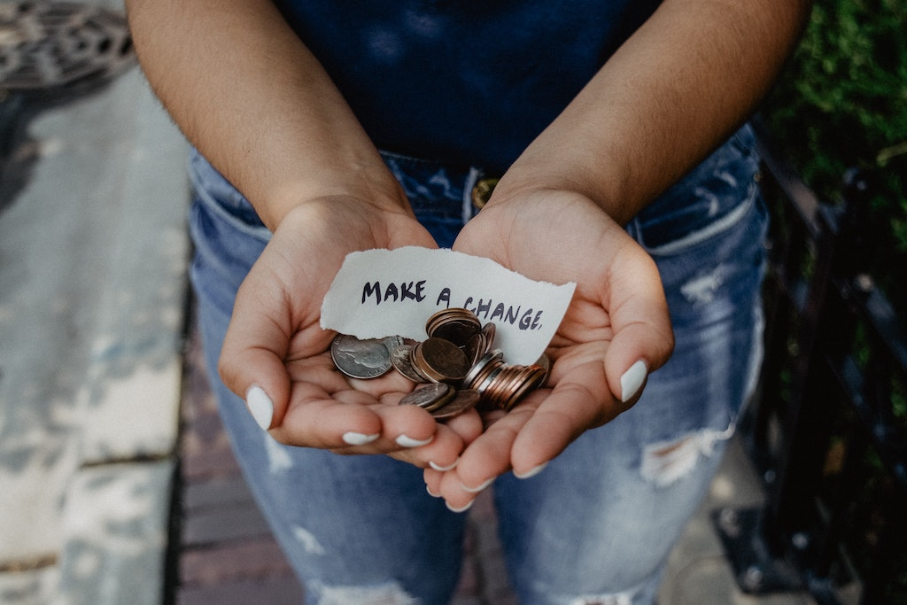"Hands holding coins and a note that says ""Make a change""."