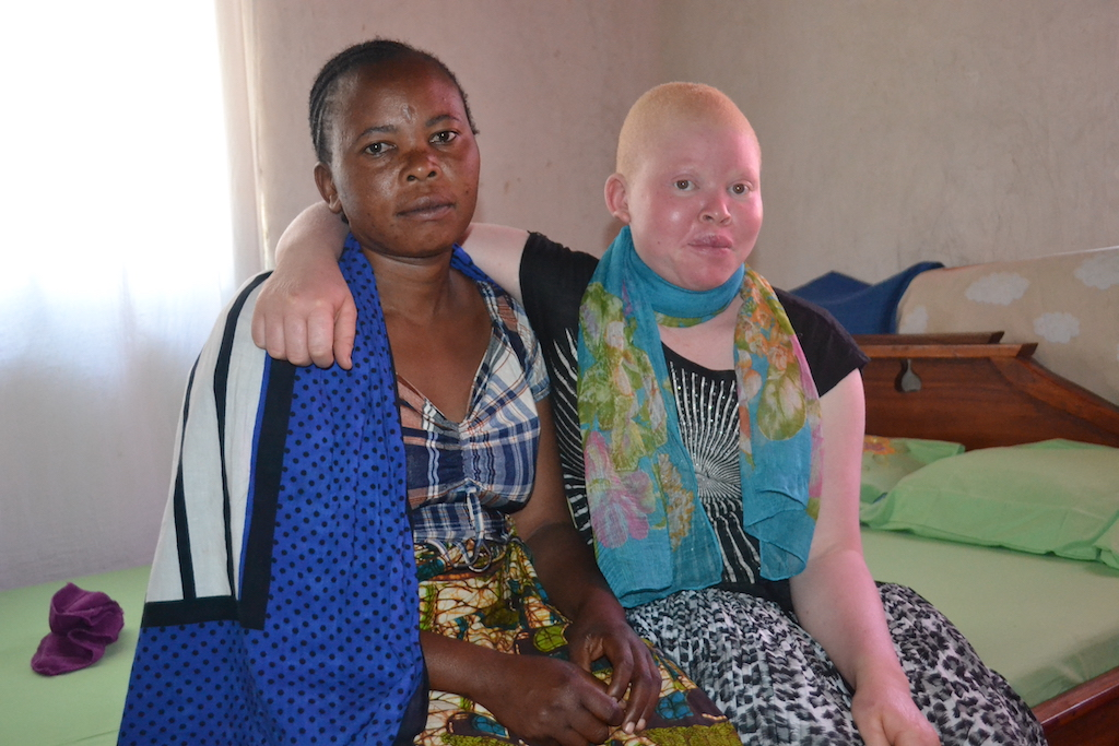 Grace and her mother sit on a bed.