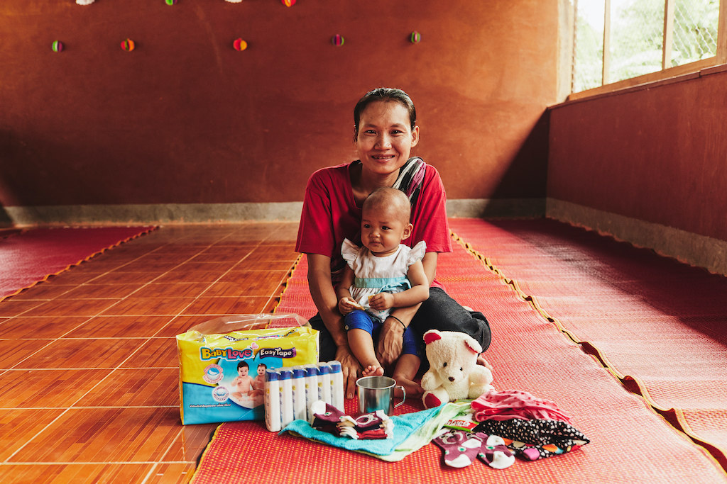 A Thai mother and her baby pose with some items they received from Compassion's Survival program.