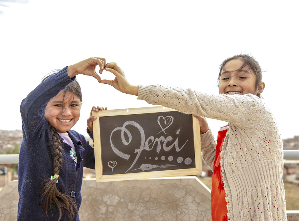"""Two Bolivian girls hold up a chalkboard with the word """"Merci"""" written on it."""