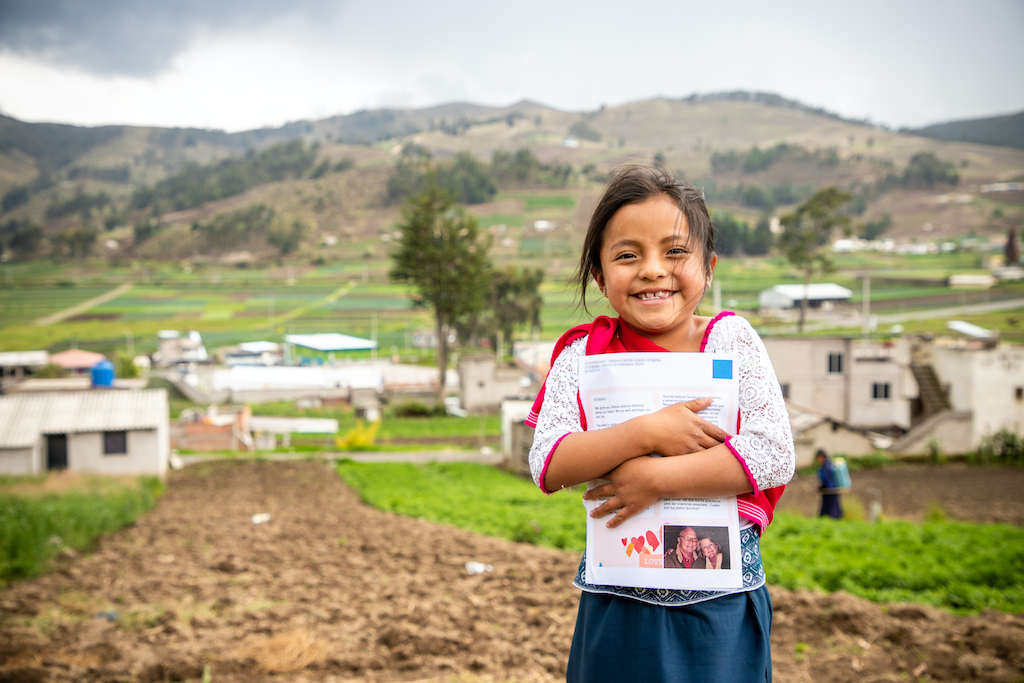 A Ecuadorian girl holds a letter from her sponsor to her chest.