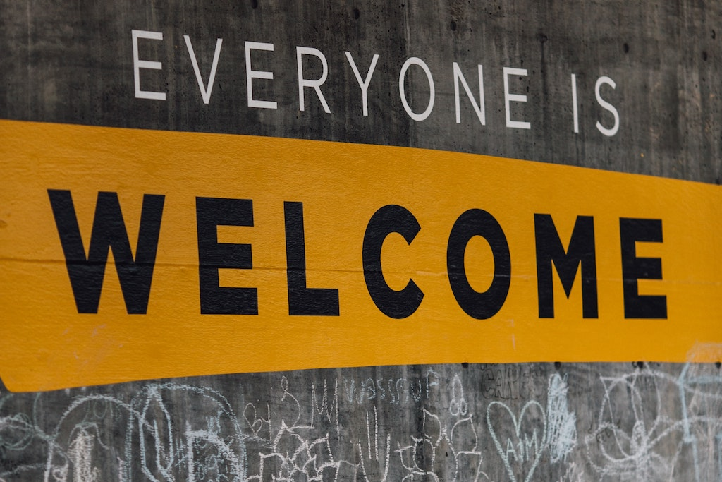 """A concrete wall with the words """"Everyone is welcome"""" painted on it."""