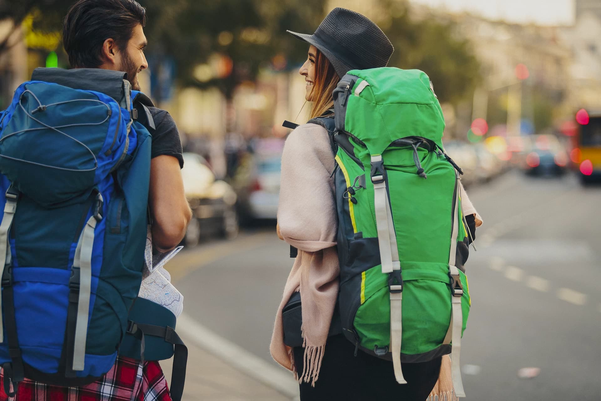 Couple smiling at each other while covered by backpacker travel insurance