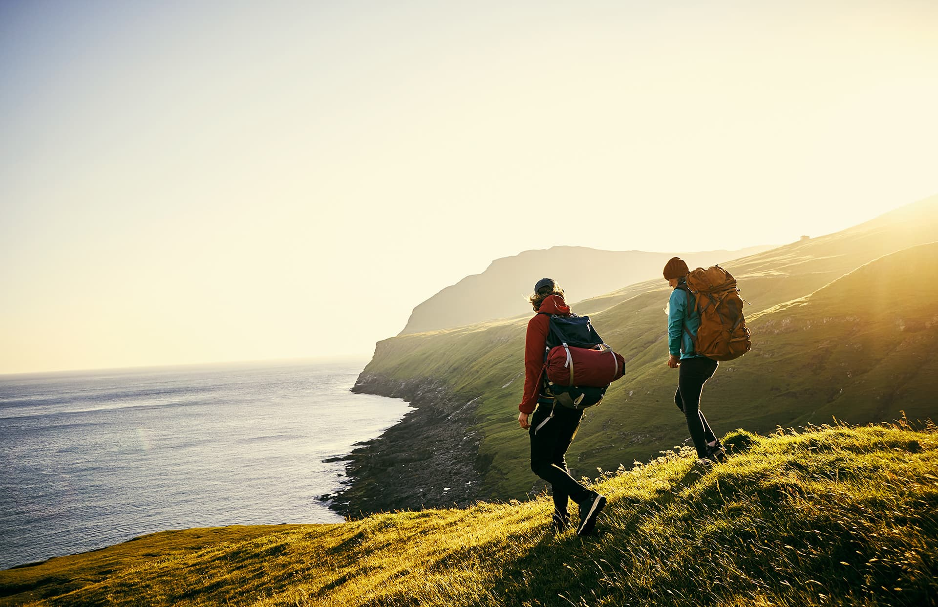 Backpacker travel insurance for two people hiking on cliffs near water