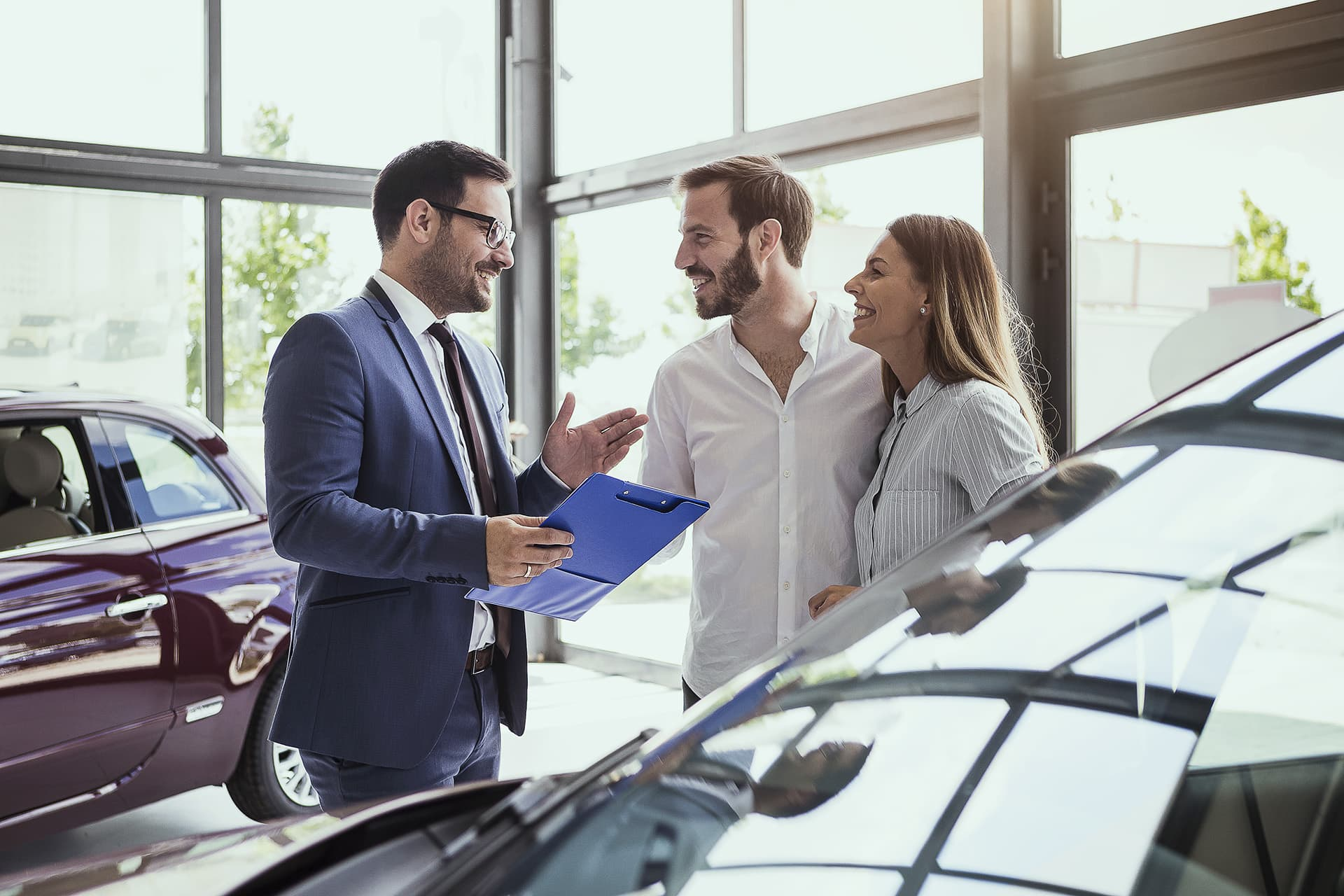 Couple speaking to a car sales man in a building with auto dealer insurance