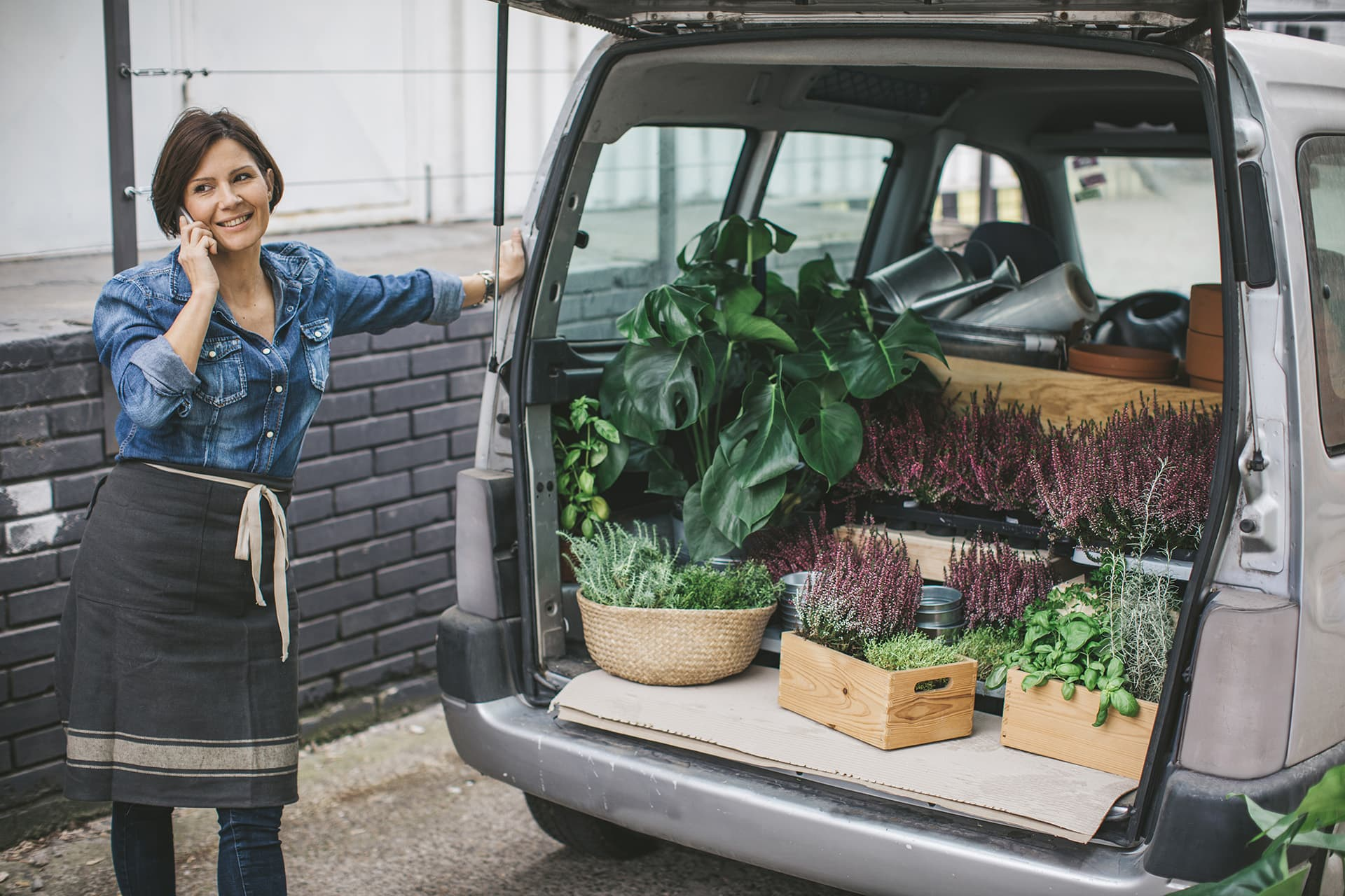 A woman on the phone with plants in the trunk of her car covered by individually rated auto insurance
