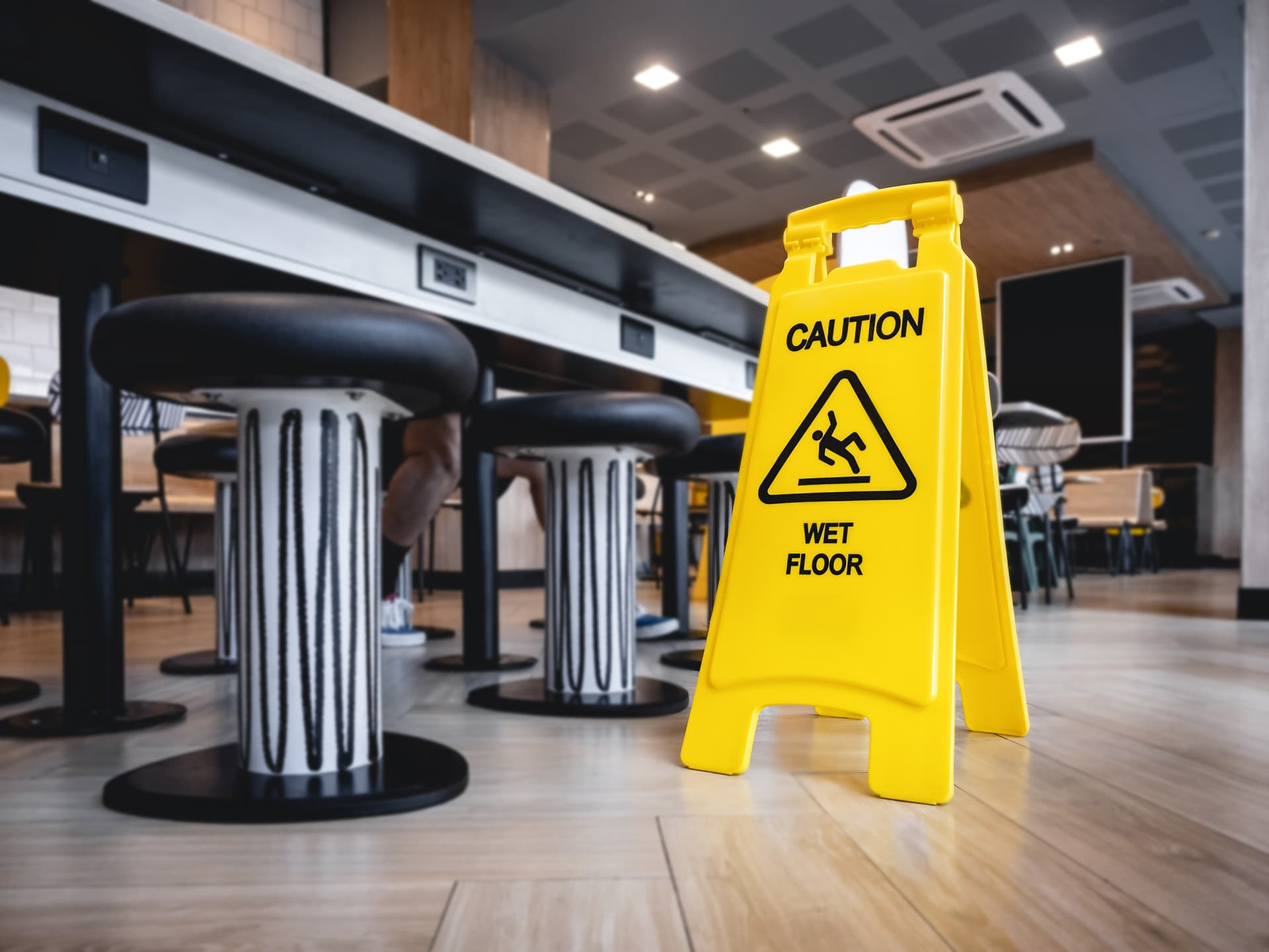 'Caution wet floor' sign in front of a table in a restaurant with commercial general liability insurance