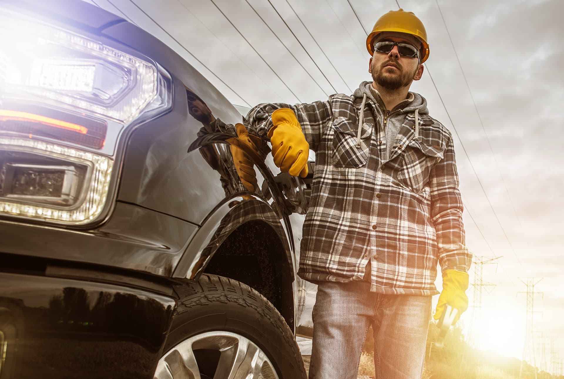 Commercial auto insurance for a man wearing a hard hat and gloves leaning on his truck
