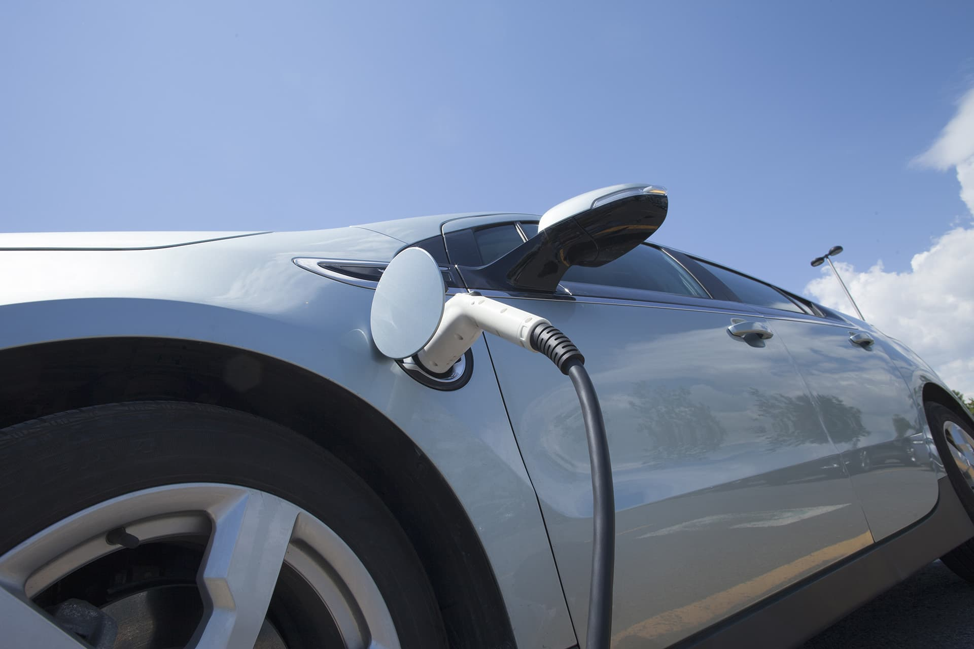 Electric vehicle insurance for silver car getting its electric battery charged