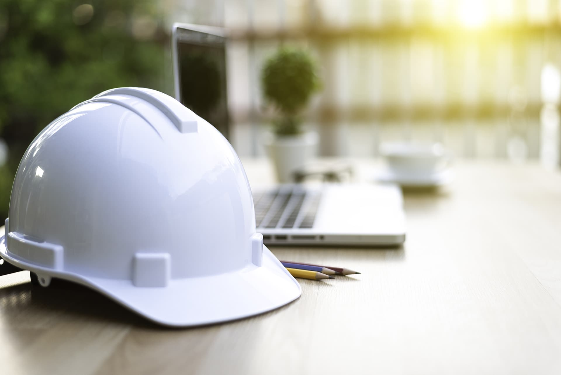 Hard hat on desk with laptop open with contractors insurance