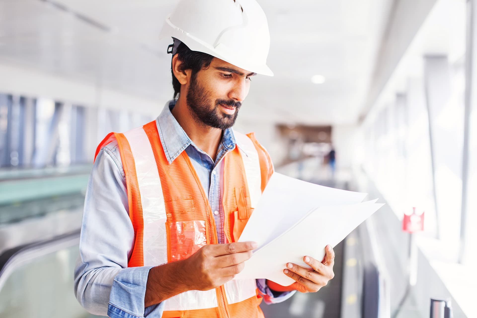 Man wearing an construction vest and hard hat, looking at his engineering insurance documents