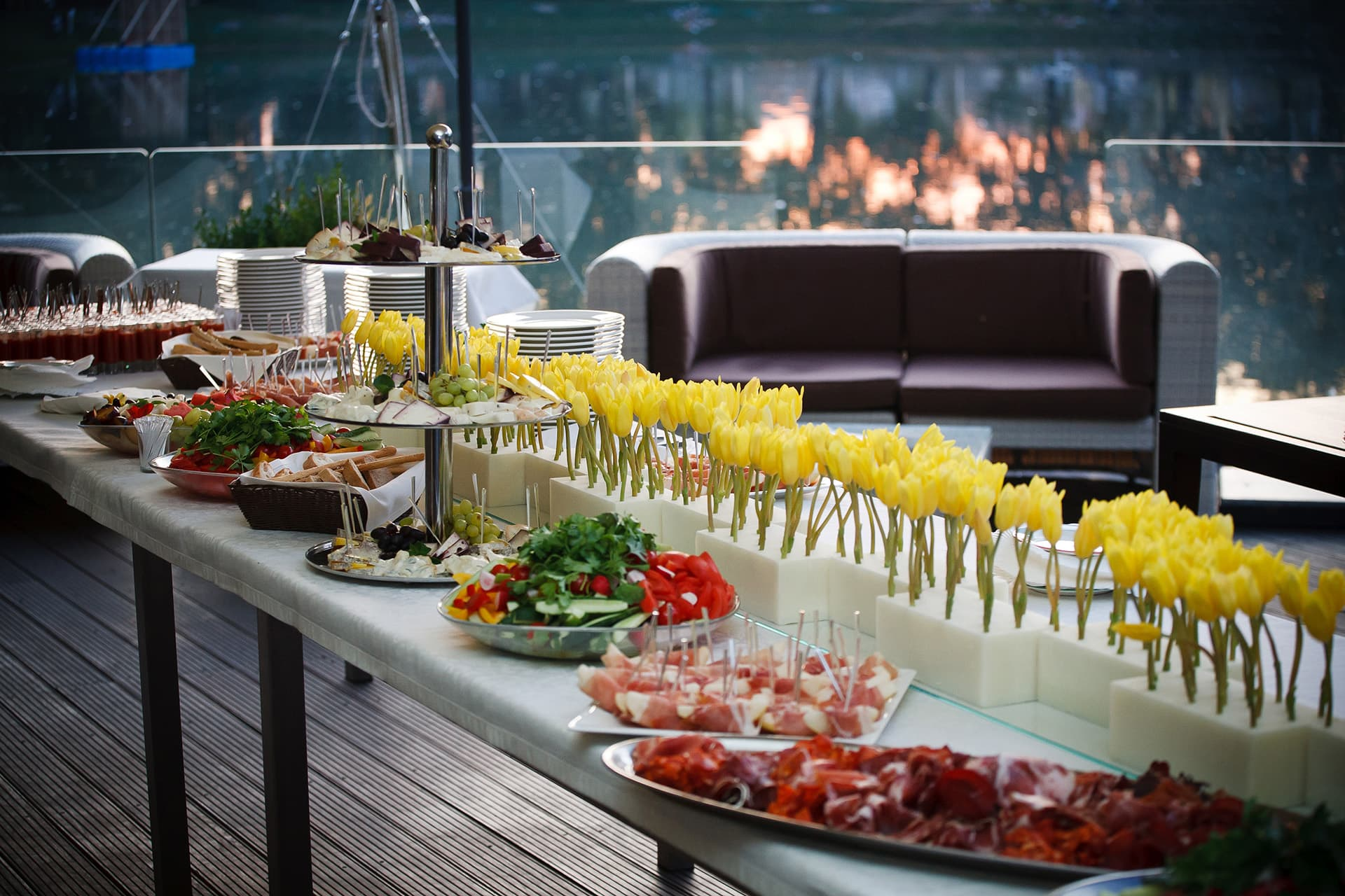 Event planner insurance with a long table of h'orderves and yellow flowers