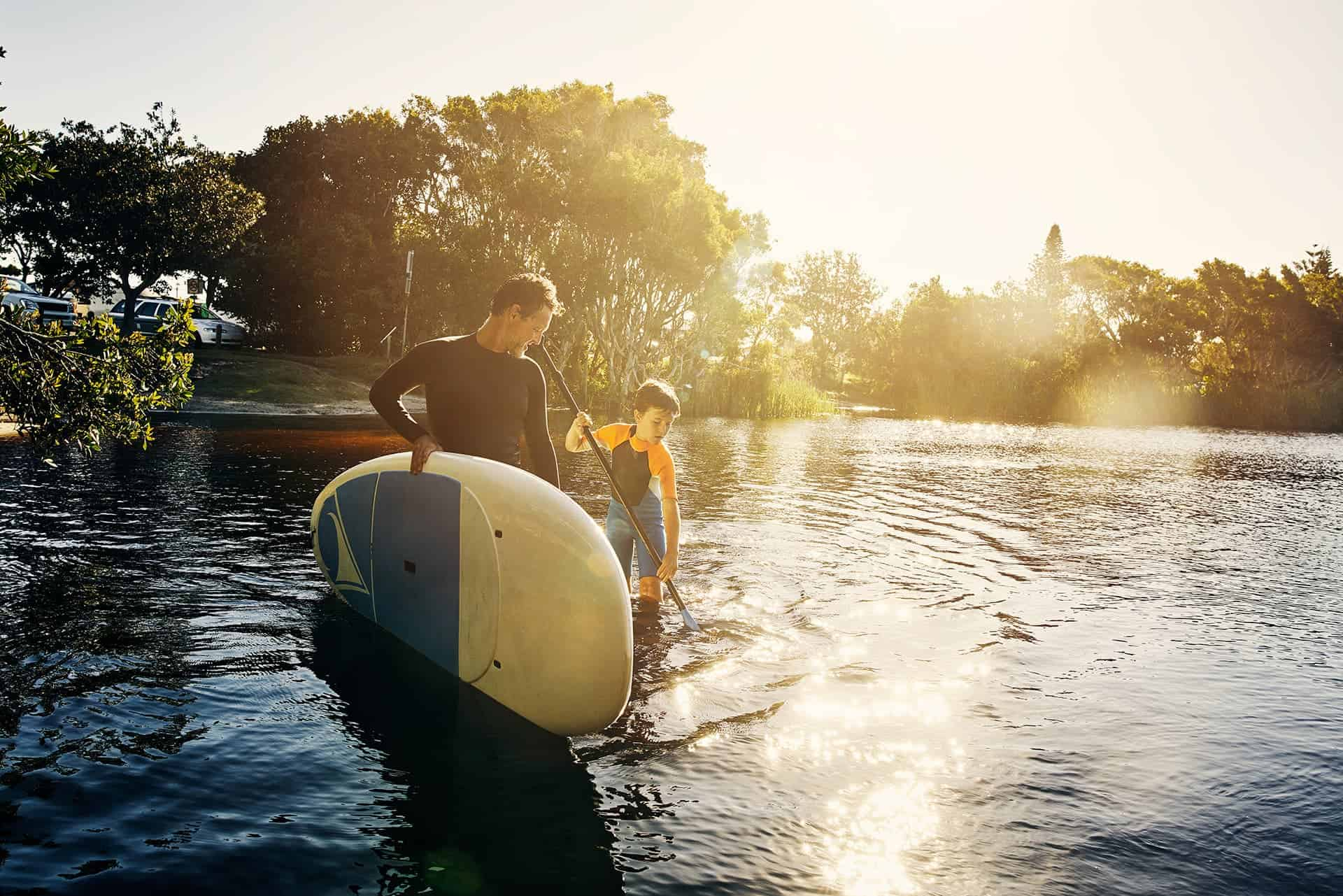 Term life insurance for a father holding a stand up paddle board while his son holds the paddle