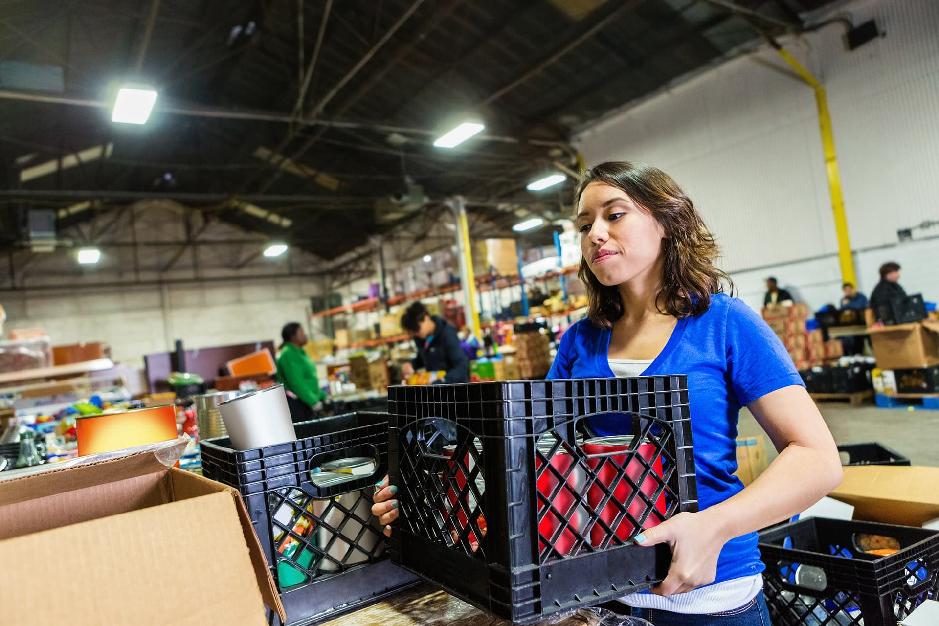 Non-profit insurance for woman carrying a crate of supplies in a warehouse