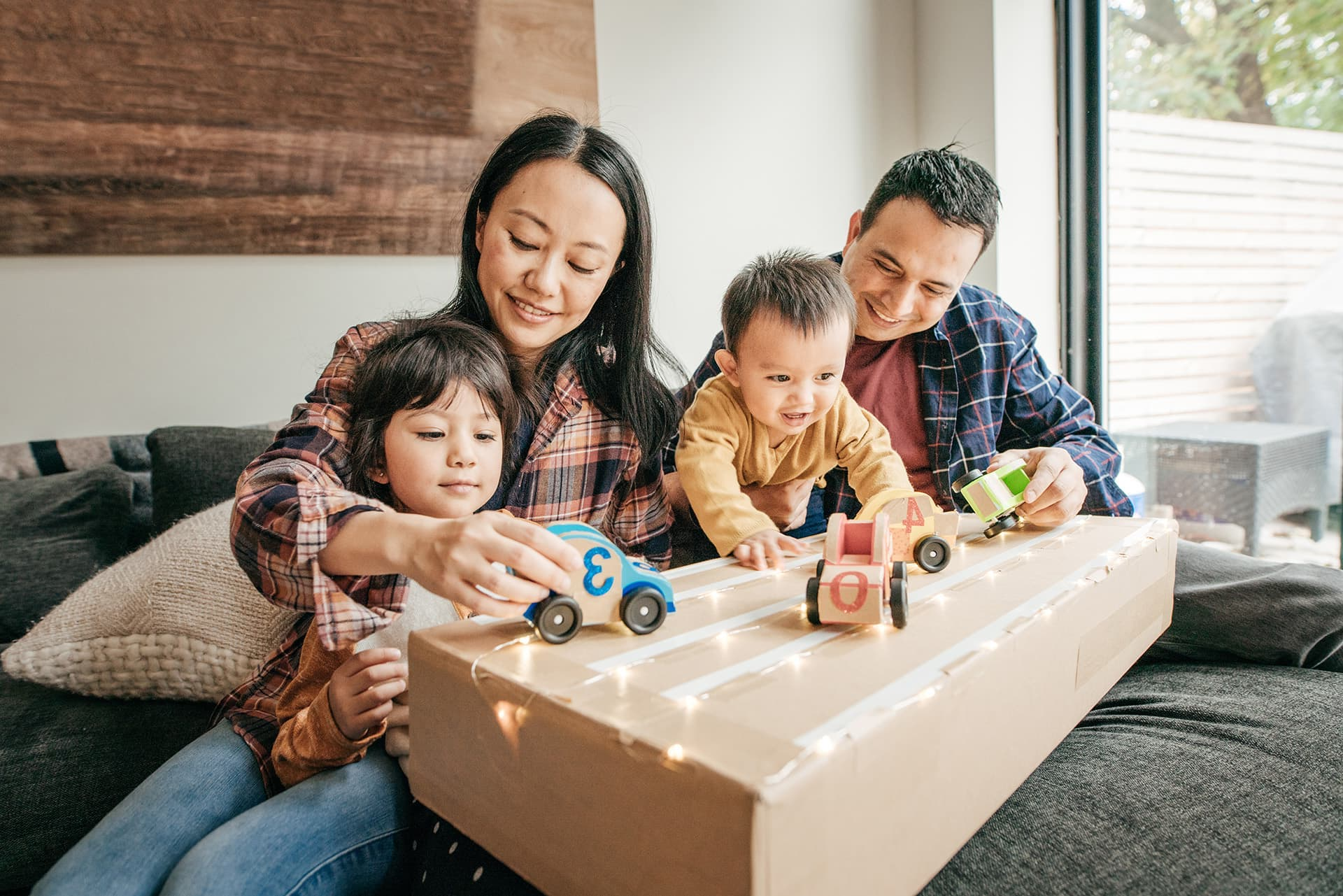 Home insurance for couple playing toy cars with their two young boys