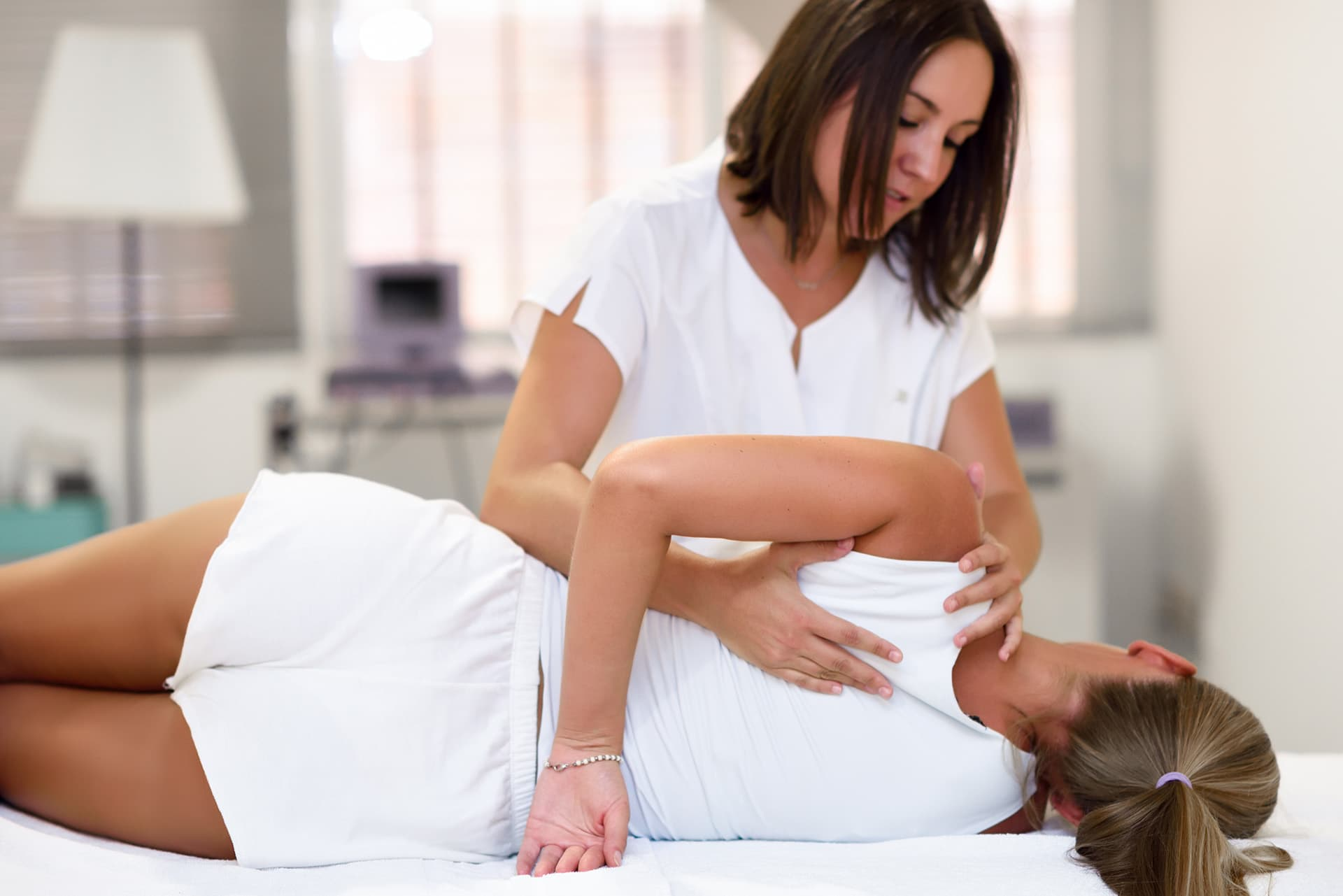 Chiropractor adjusting a patient laying down with medical professional liability insurance