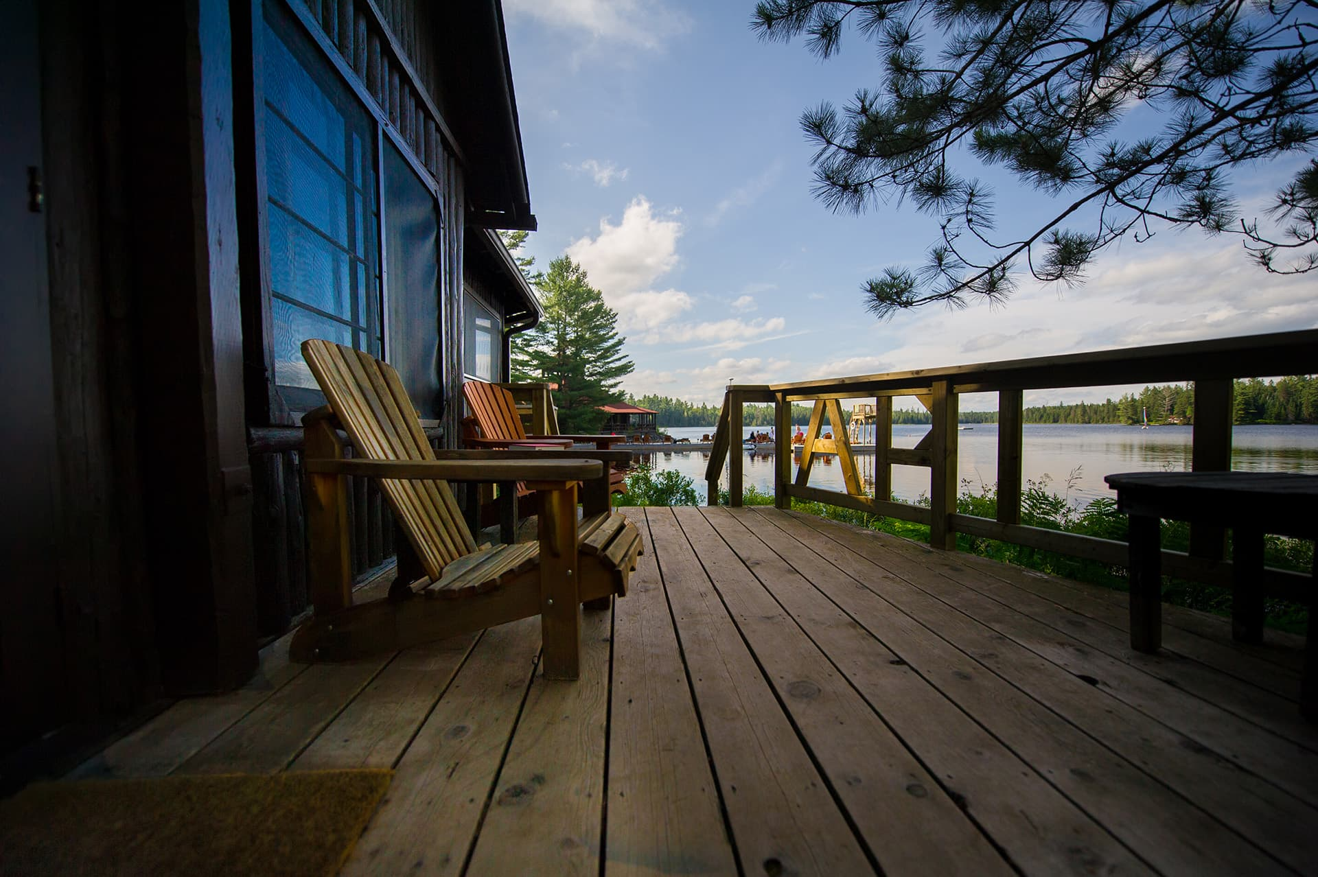 High risk home insurance for cottage next to a lake with a porch and Muskoka chairs