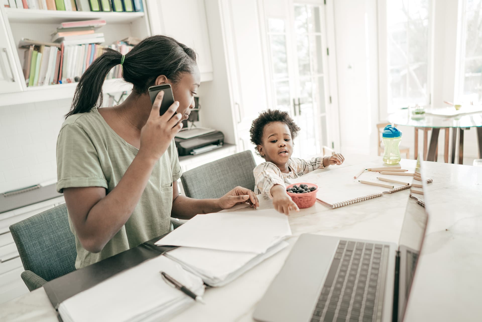 Woman sitting next to her child, talking on the phone, with home business insurance documents in front of her