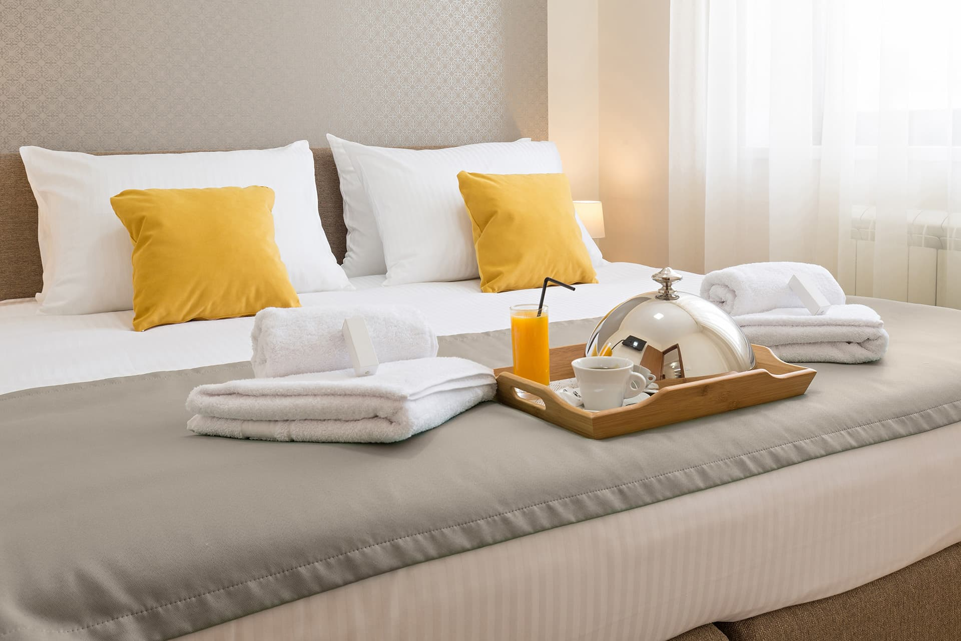 Bed with towels and room service tray at a hotel with hotel insurance