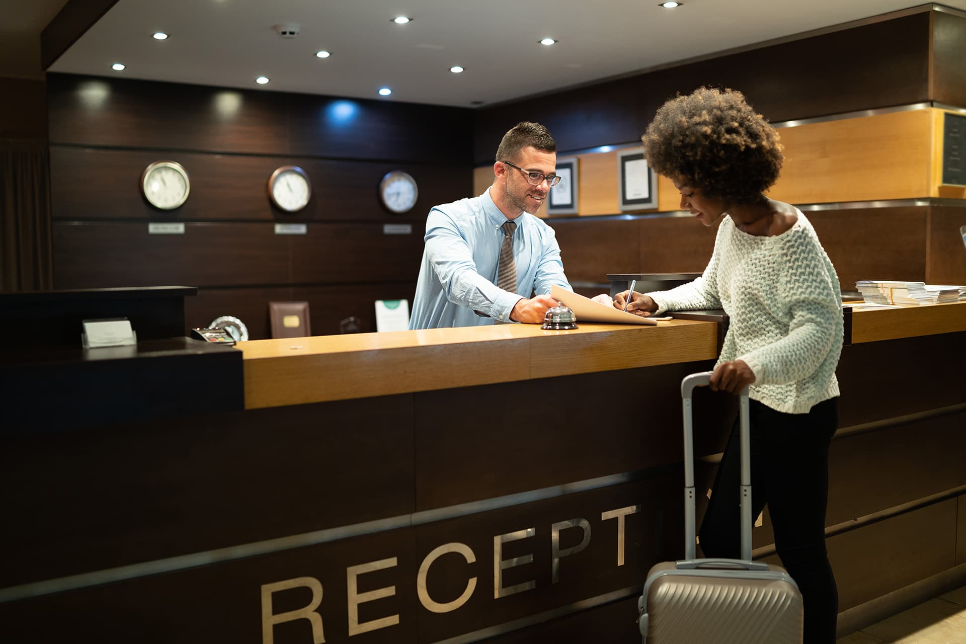 Man at a reception desk helping a woman checking into a hotel with hotel insurance