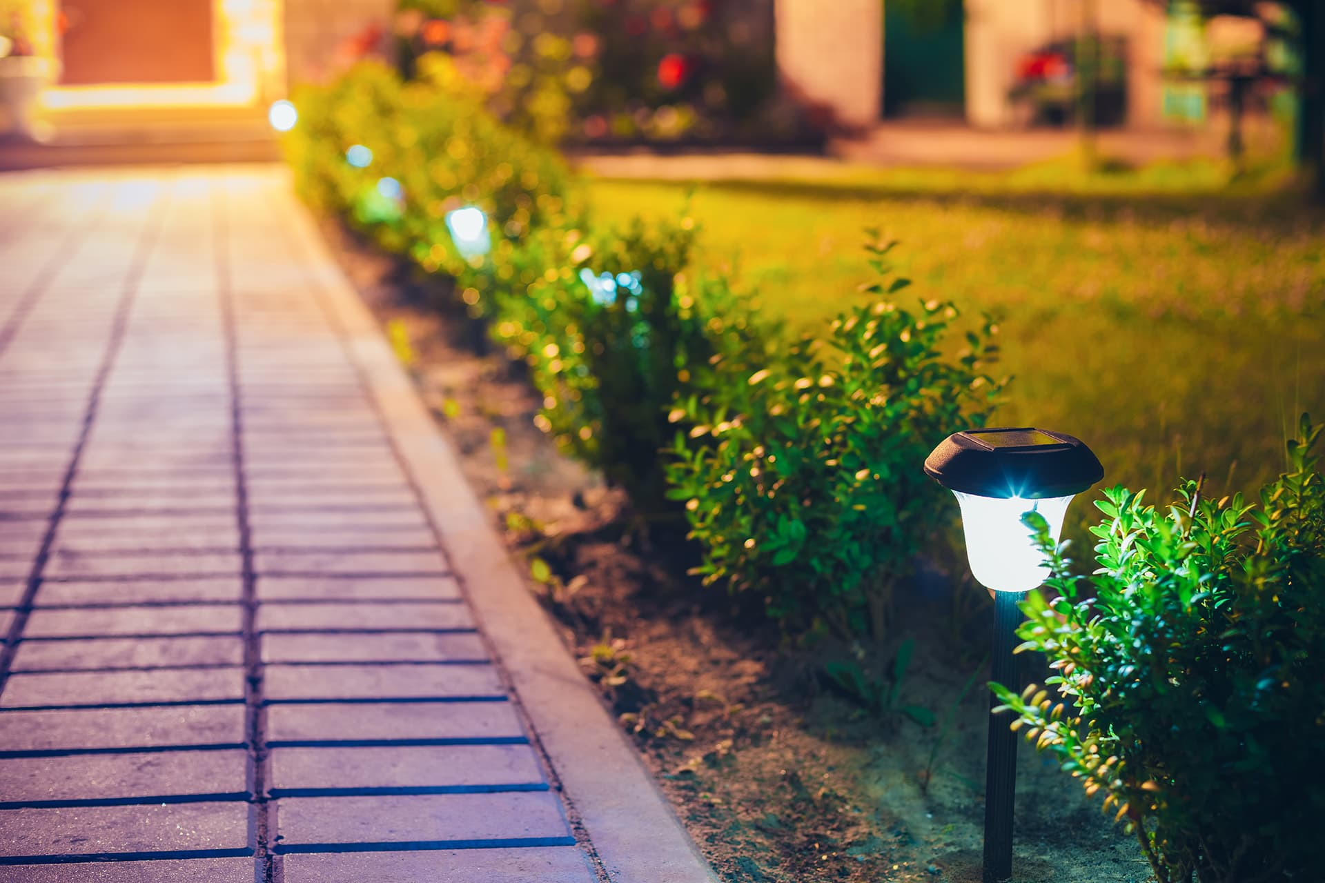 Interlocked pathway with shrubs and ground lighting installed by a company with landscaping insurance