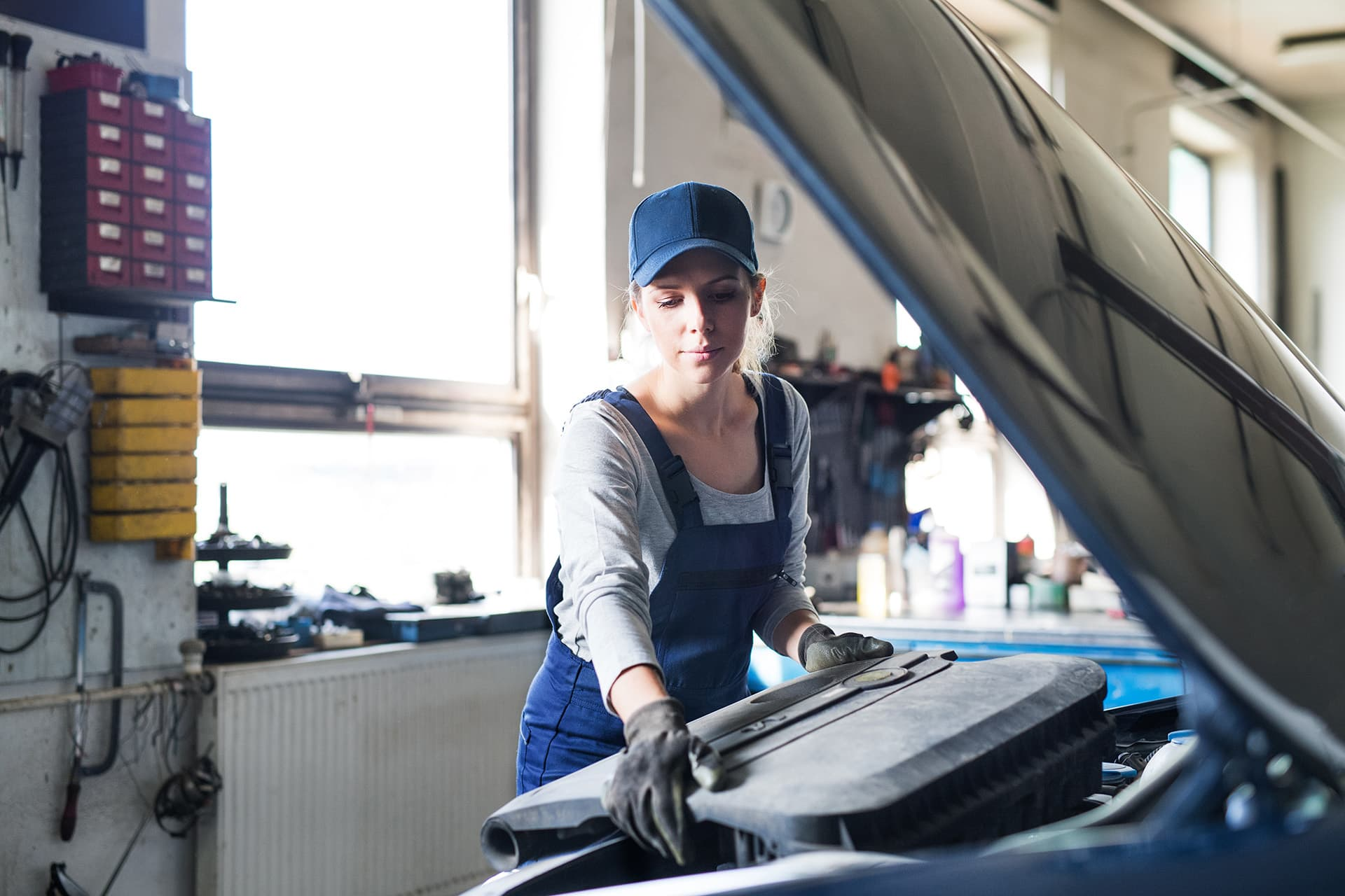 Woman with auto garage insurance fixing motor under the hood of a car