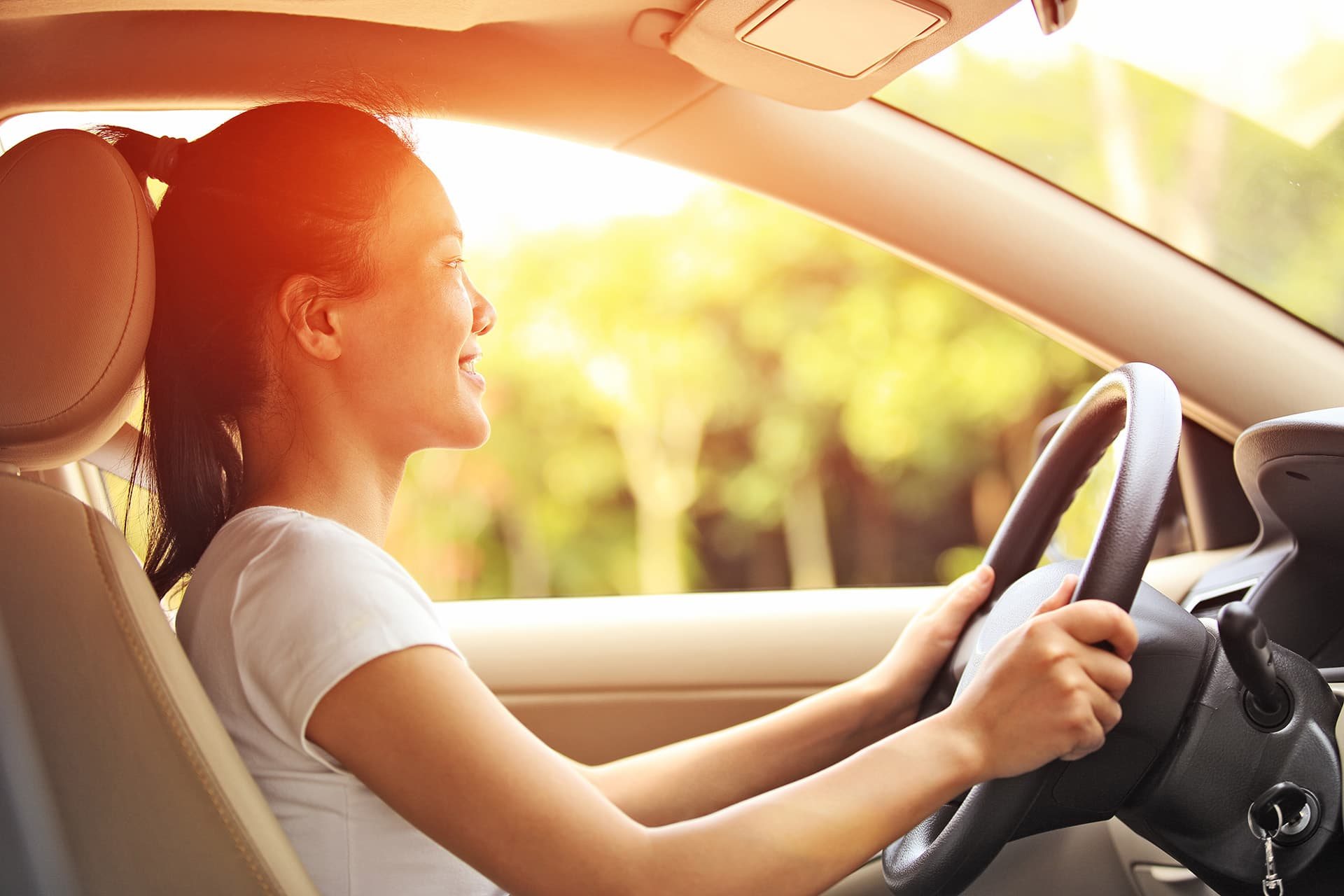 Young woman with new driver insurance driving a car with leather interior