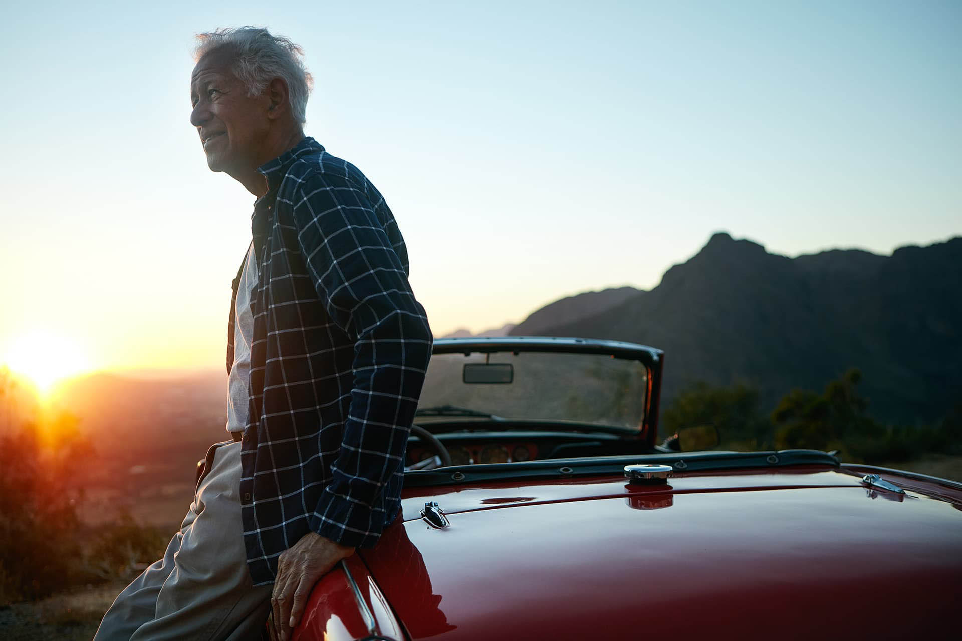 Elderly man with over 50 car insurance leaning on his red convertible car