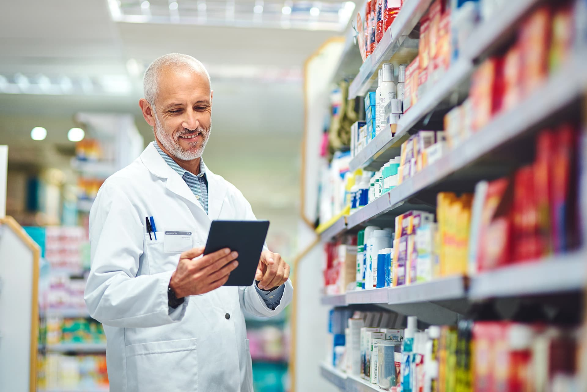 Pharmacist standing in an aisle of medicine, looking at his medical professional liability insurance on his tablet