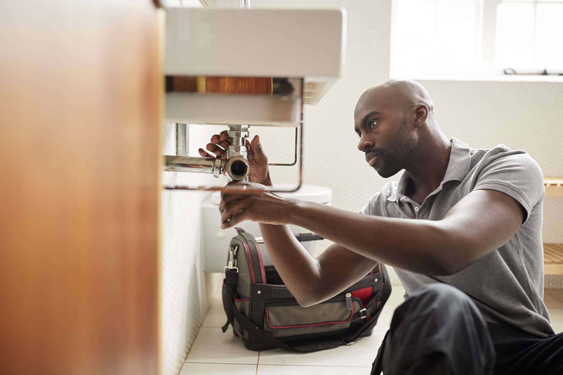 Man with plumber's insurance fixing pipes under a sink