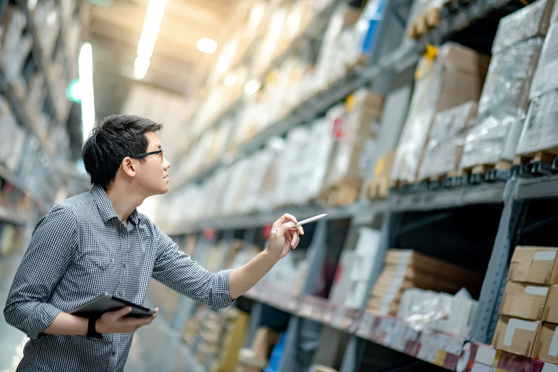 Man checking inventory in warehouse with product liability insurance