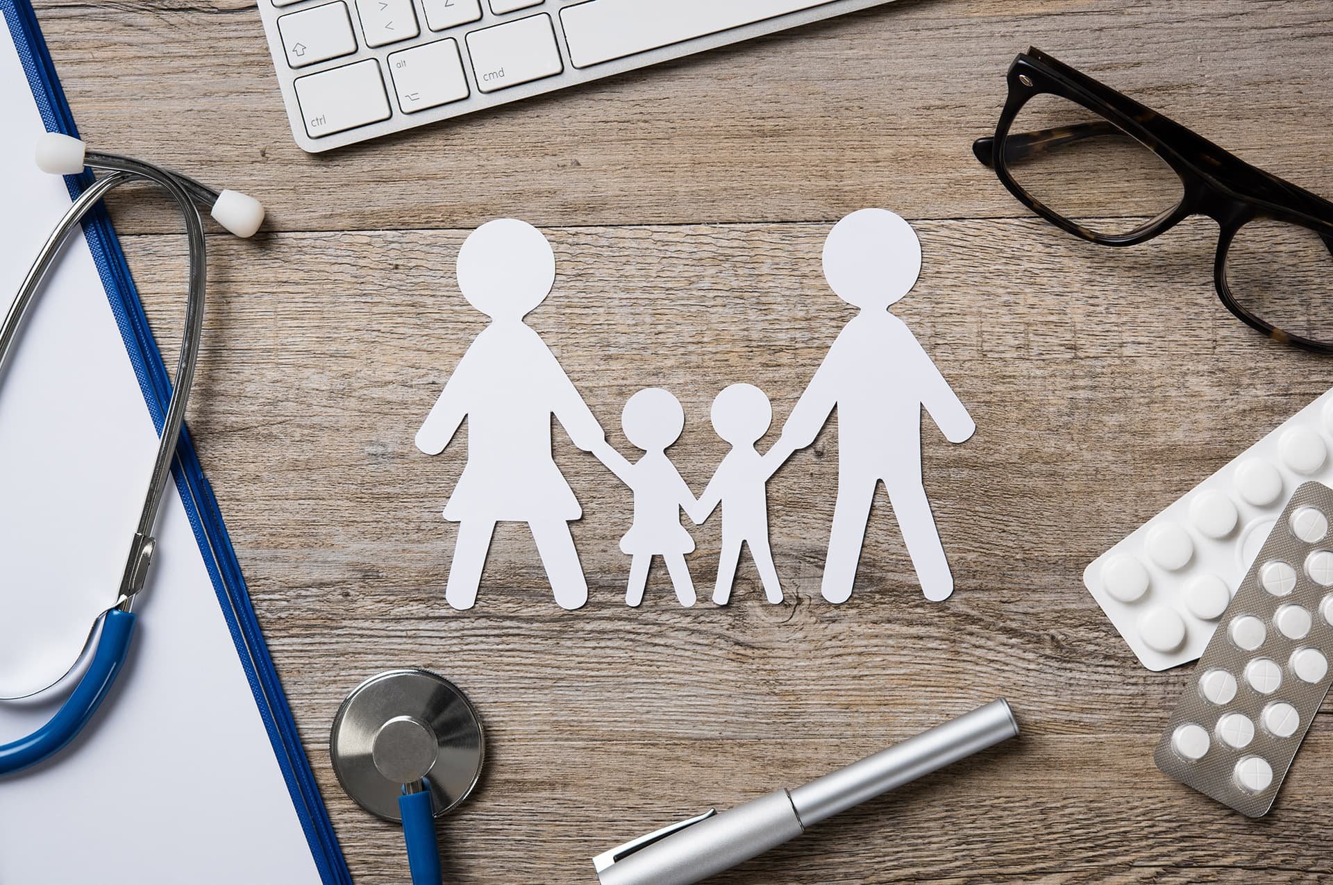 Paper cut out of family on a doctor's desk with professional liability insurance