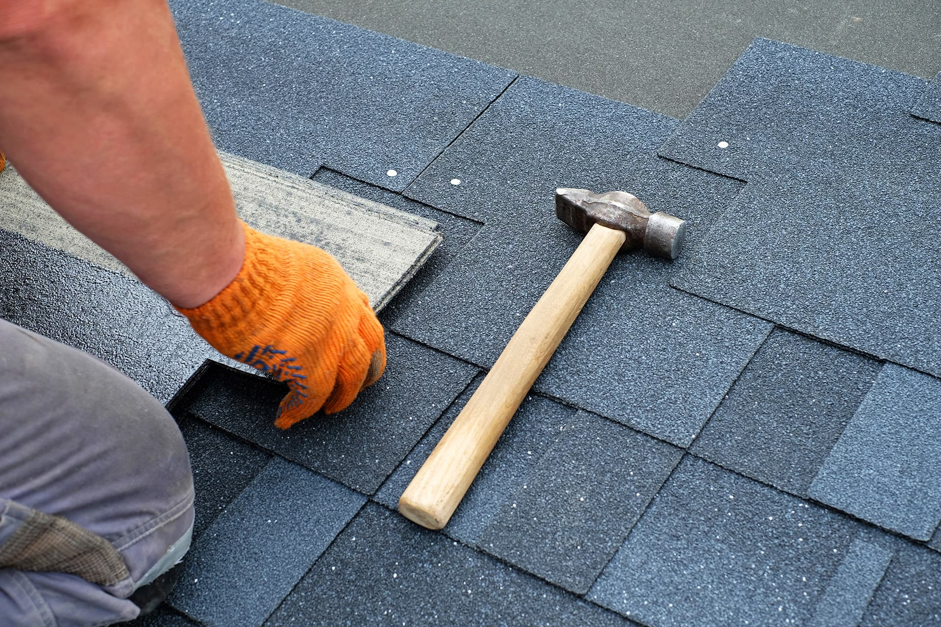 Person with roofing contractor insurance placing shingles on a roof next to a hammer