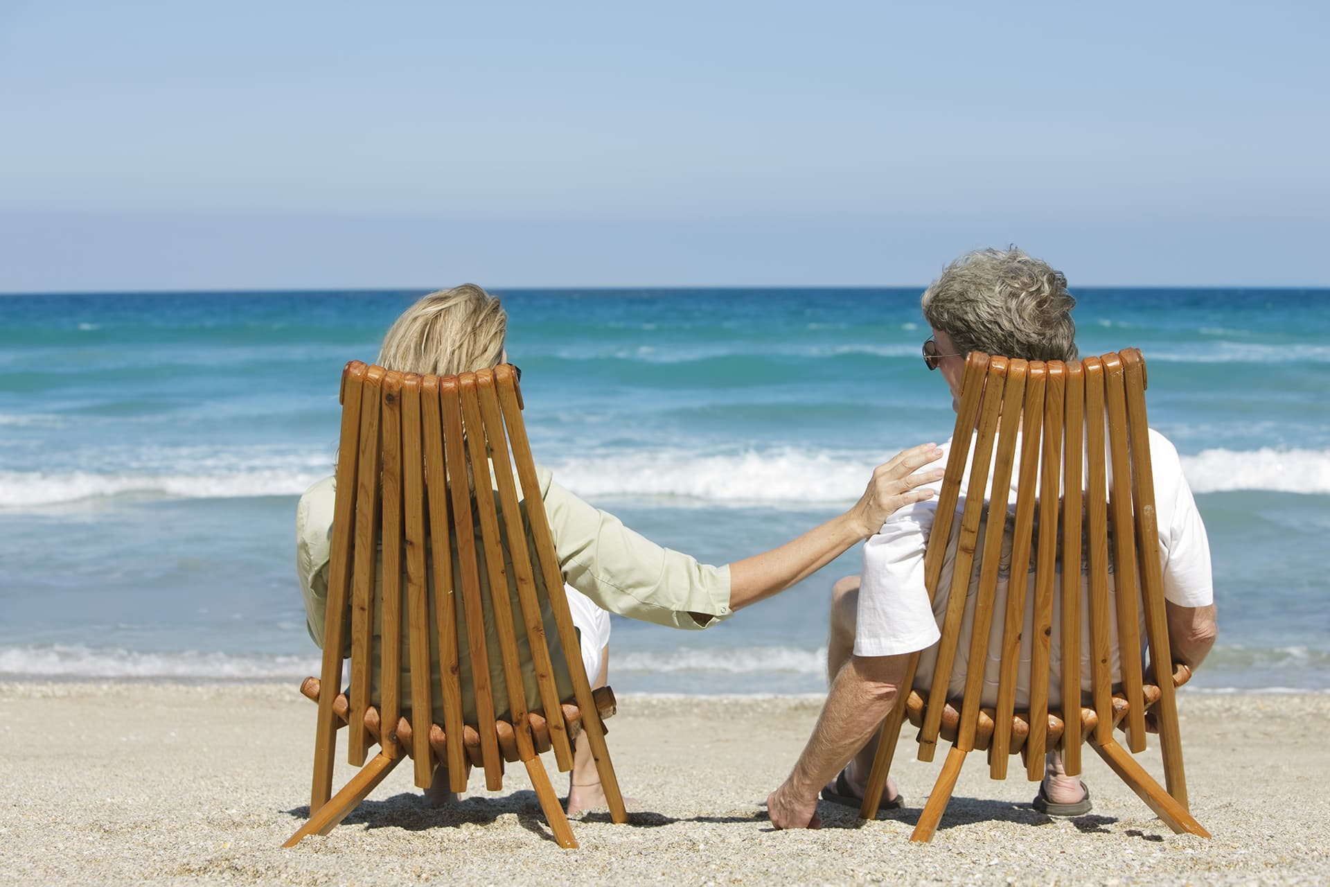 Couple sitting in chairs on a beach with special limits insurance