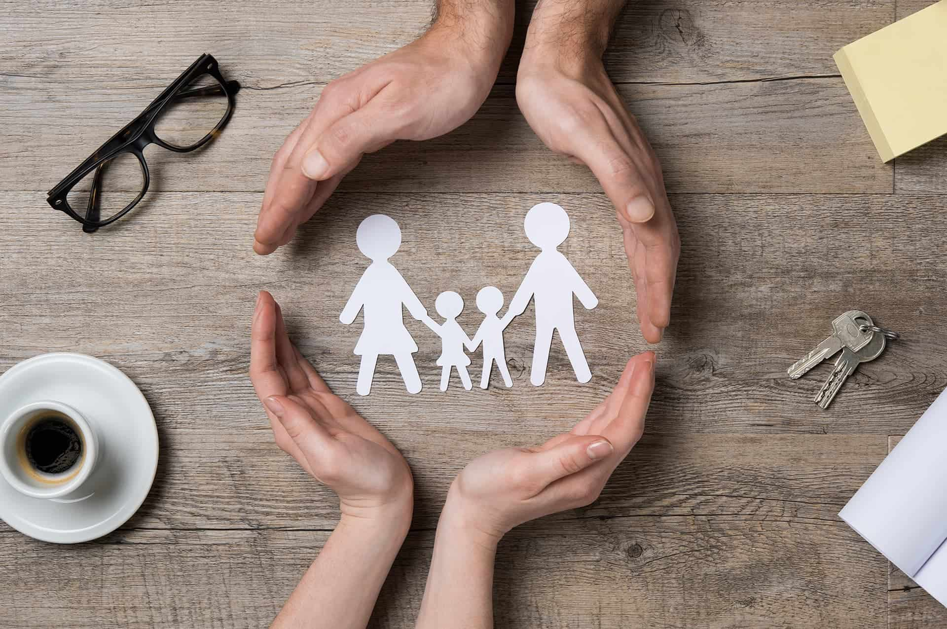 Two people placing their hands around a paper cut out of a family with term life insurance