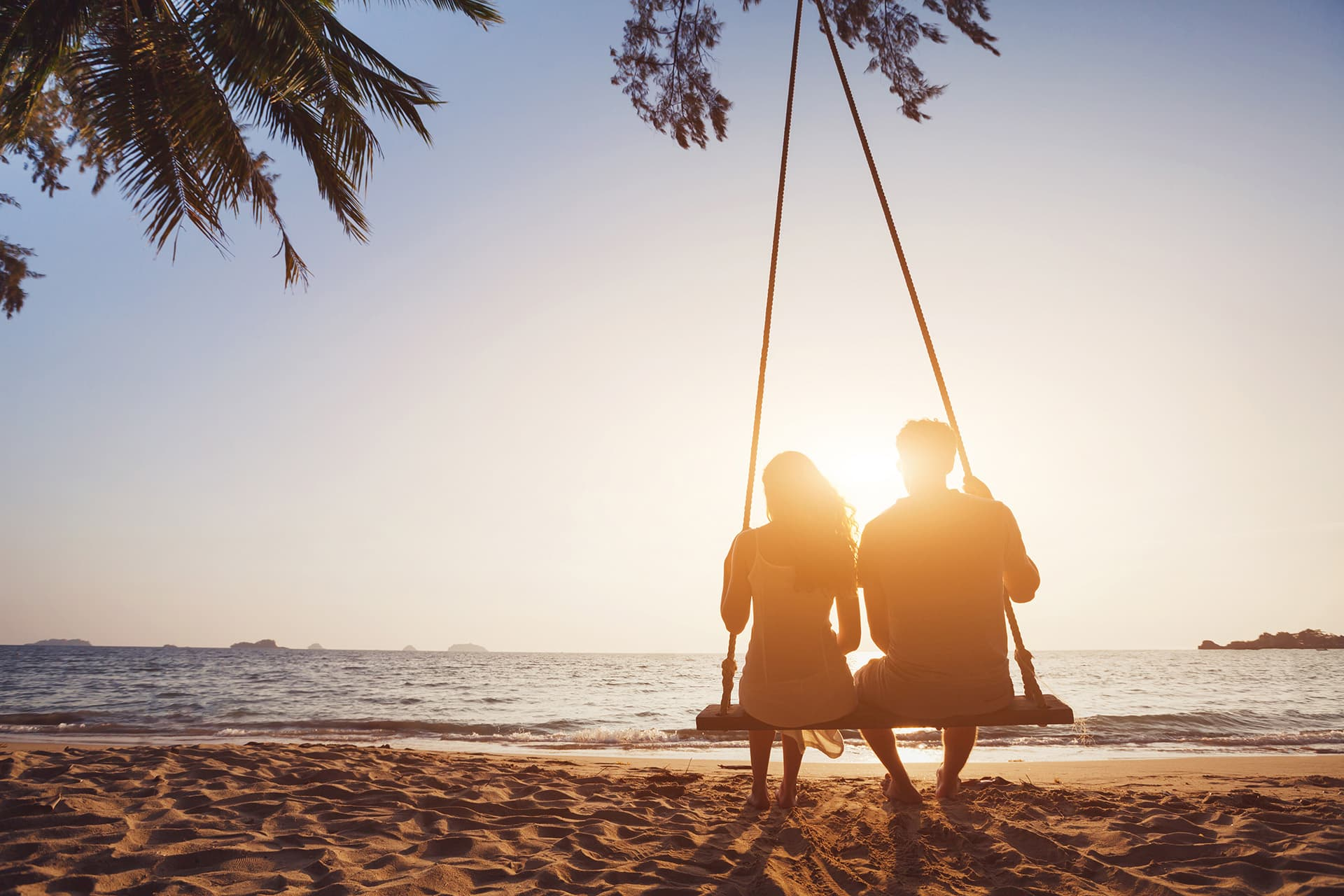 Couple sitting on a swing at a beach with travel insurance