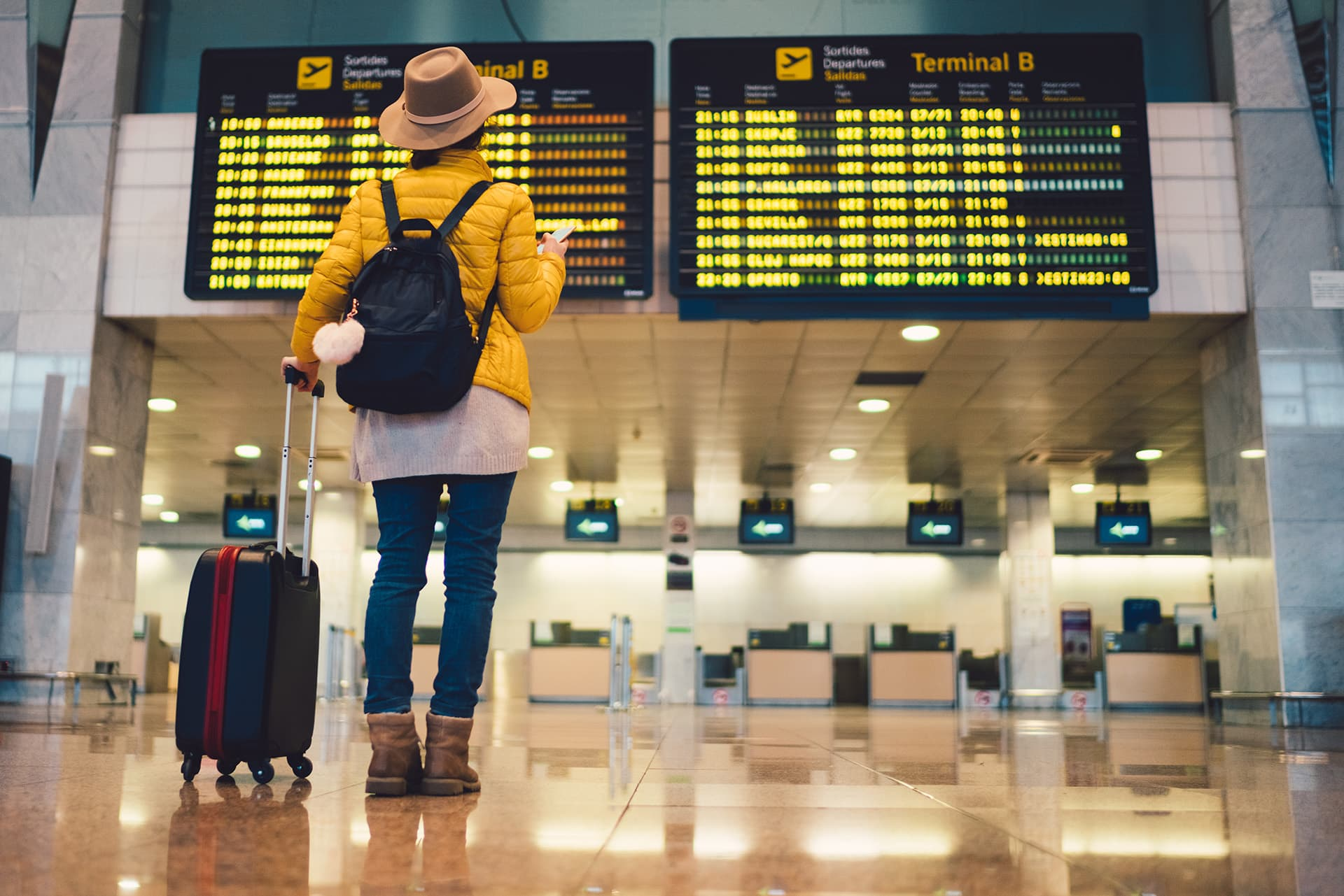 Travel insurance for woman checking the departure board at an airport