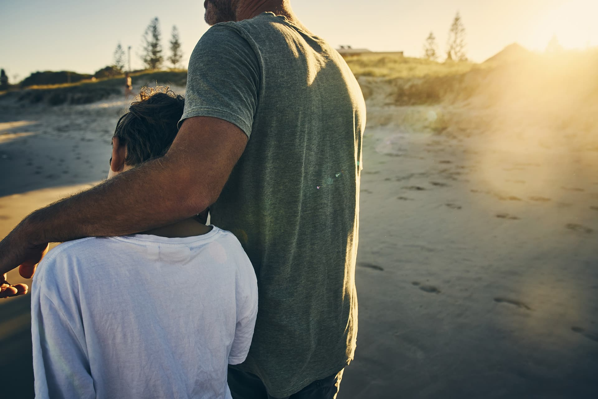 Universal life insurance for a father with his arm around his son walking on sand