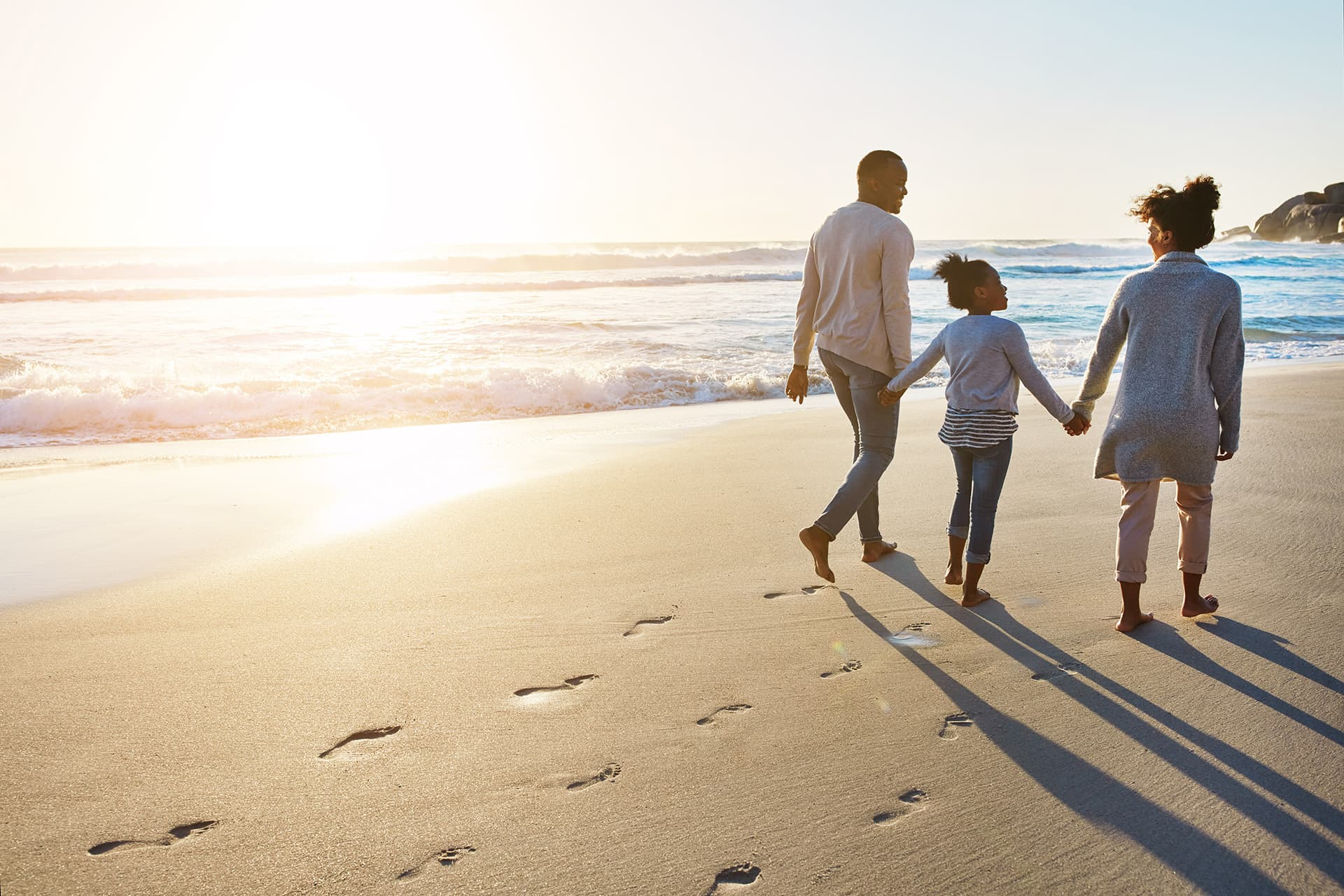 A mother, father and daughter with universal life insurance walking on a beach holding hands