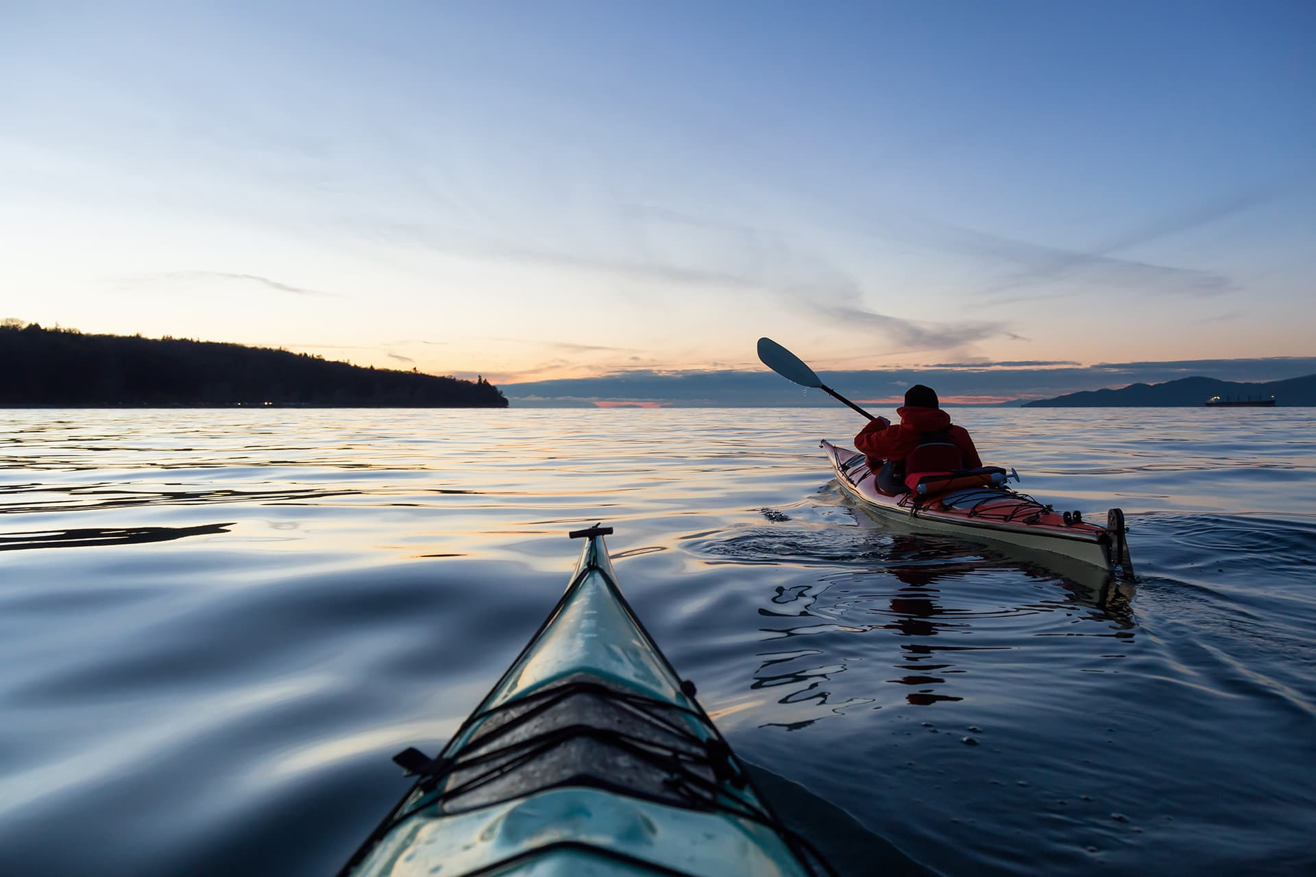 Two people kayaking on water with Canada visitor insurance