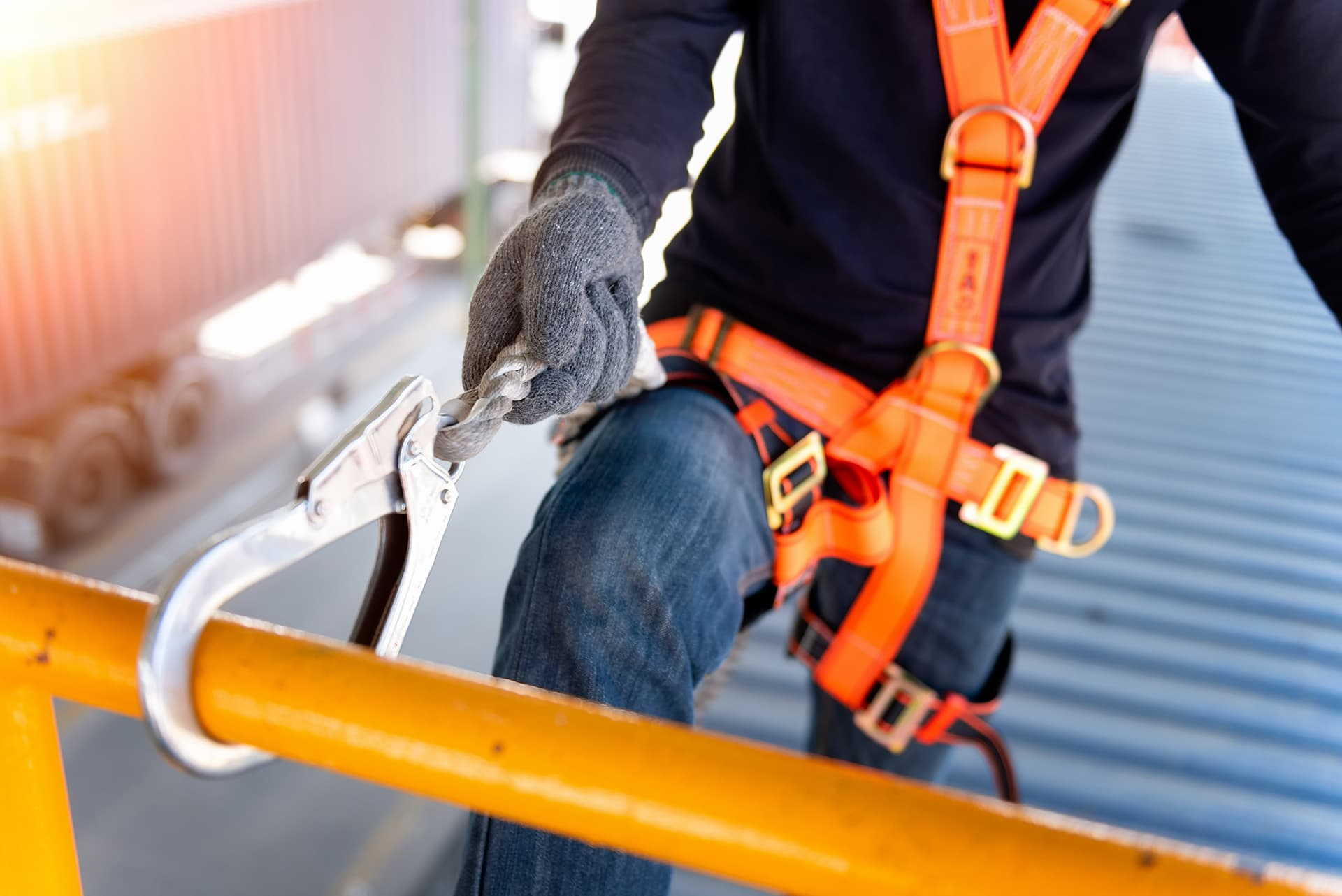 Man with roofing contractor insurance wearing a harness and strapped to a pole