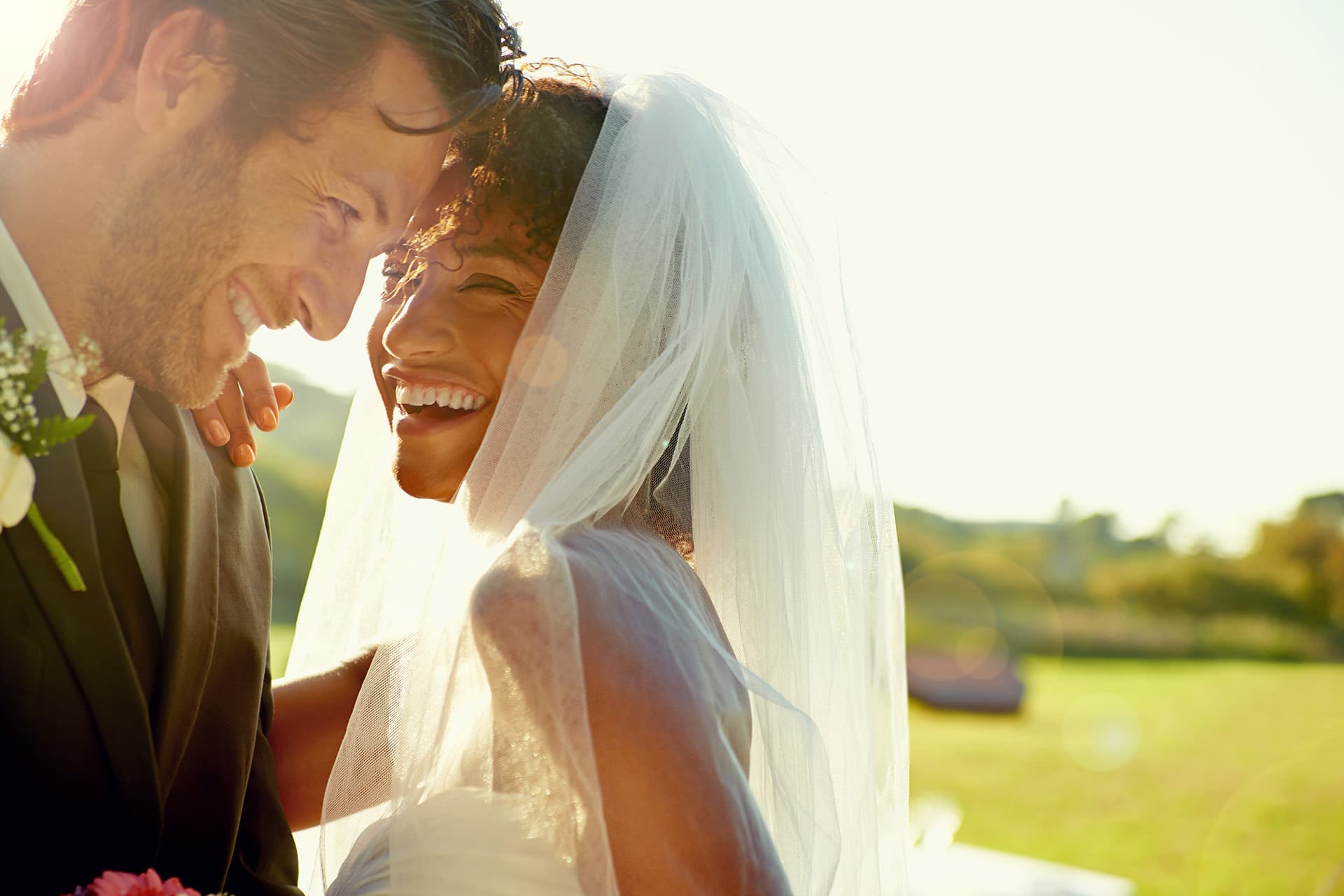 Life insurance for a bride and groom smiling and looking at each other