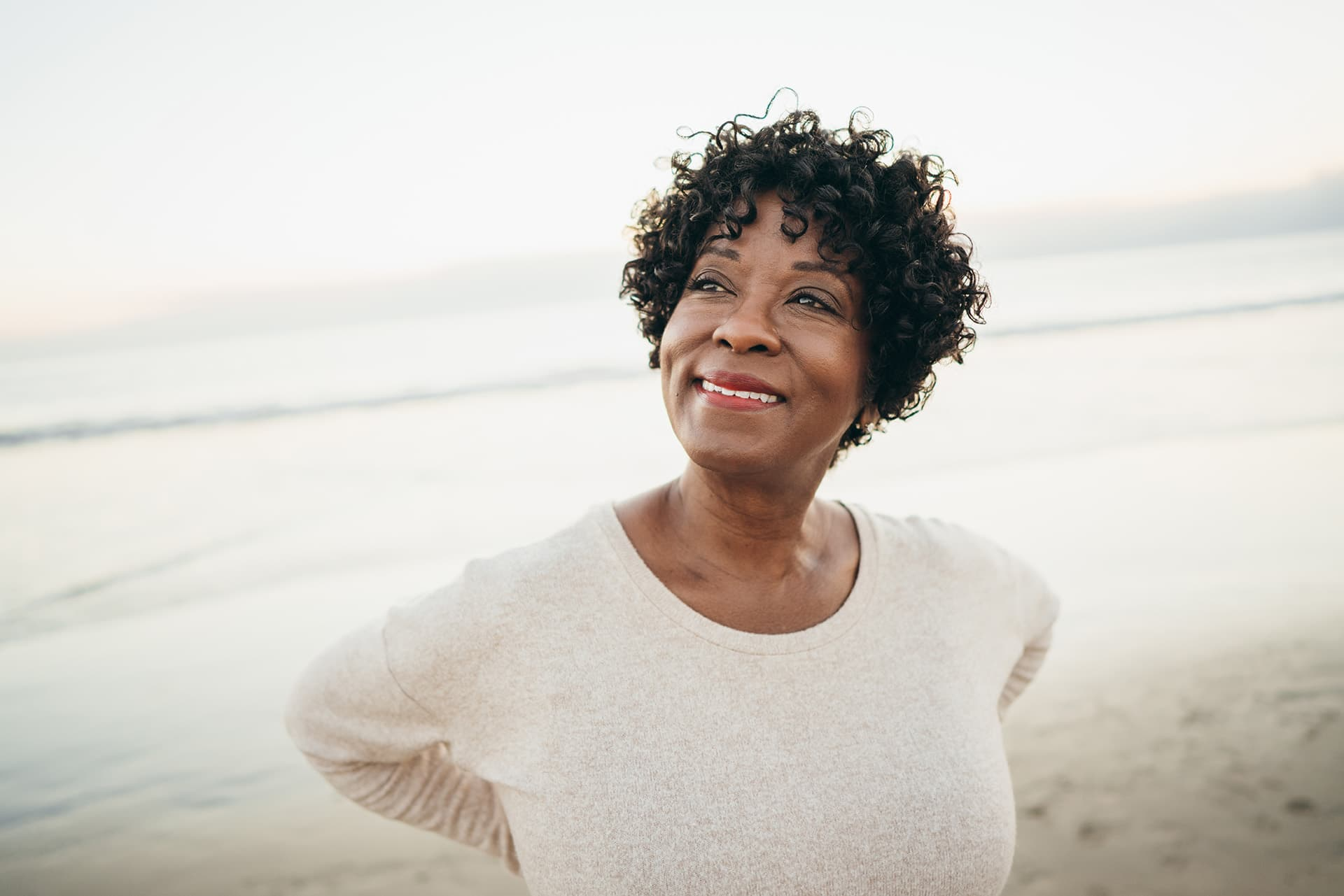 Woman with whole life insurance smiling on a beach