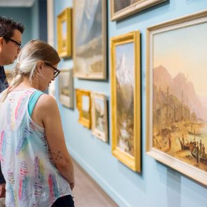 two people with glasses peering at a wall full of paintings in golden frames