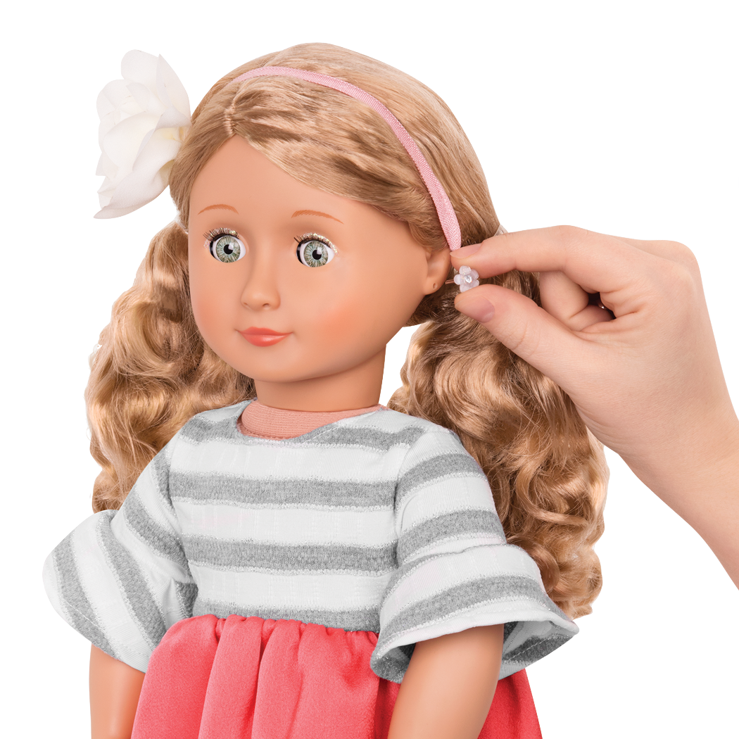 Close up of adding earrings to doll