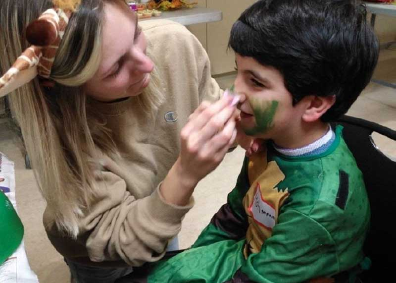 Newcomer child getting face painted